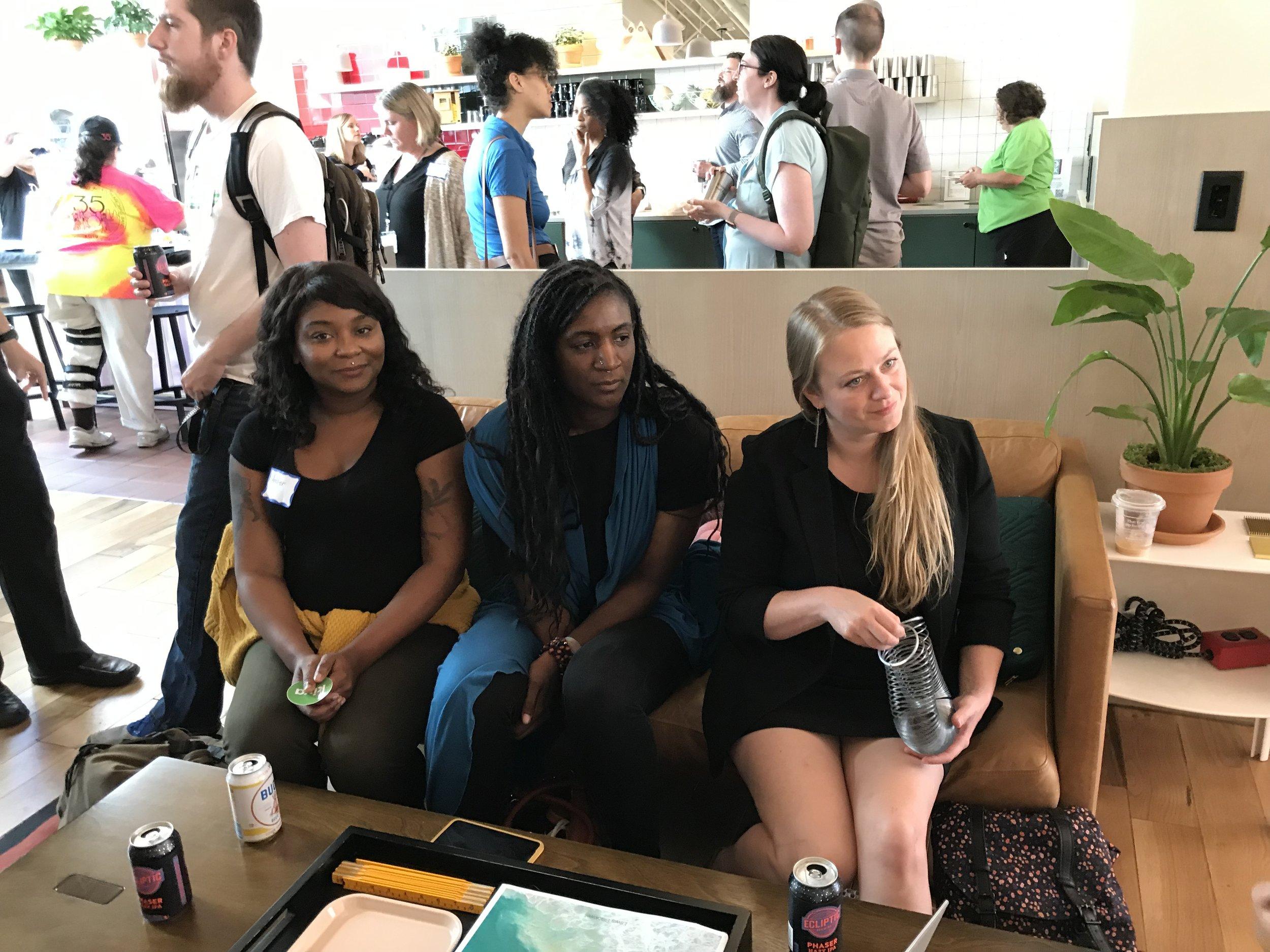 Three women sitting and listening to speakers.JPG