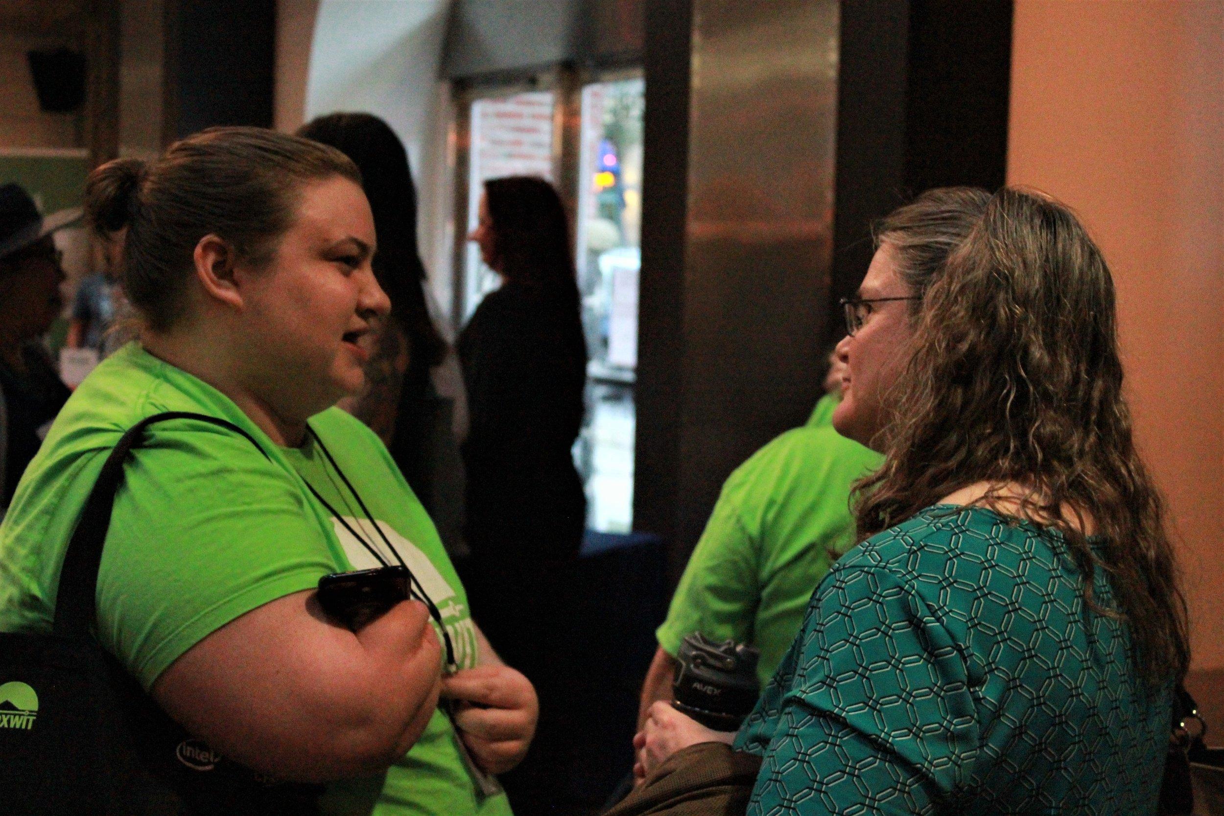 volunteers talking with attendee.jpg