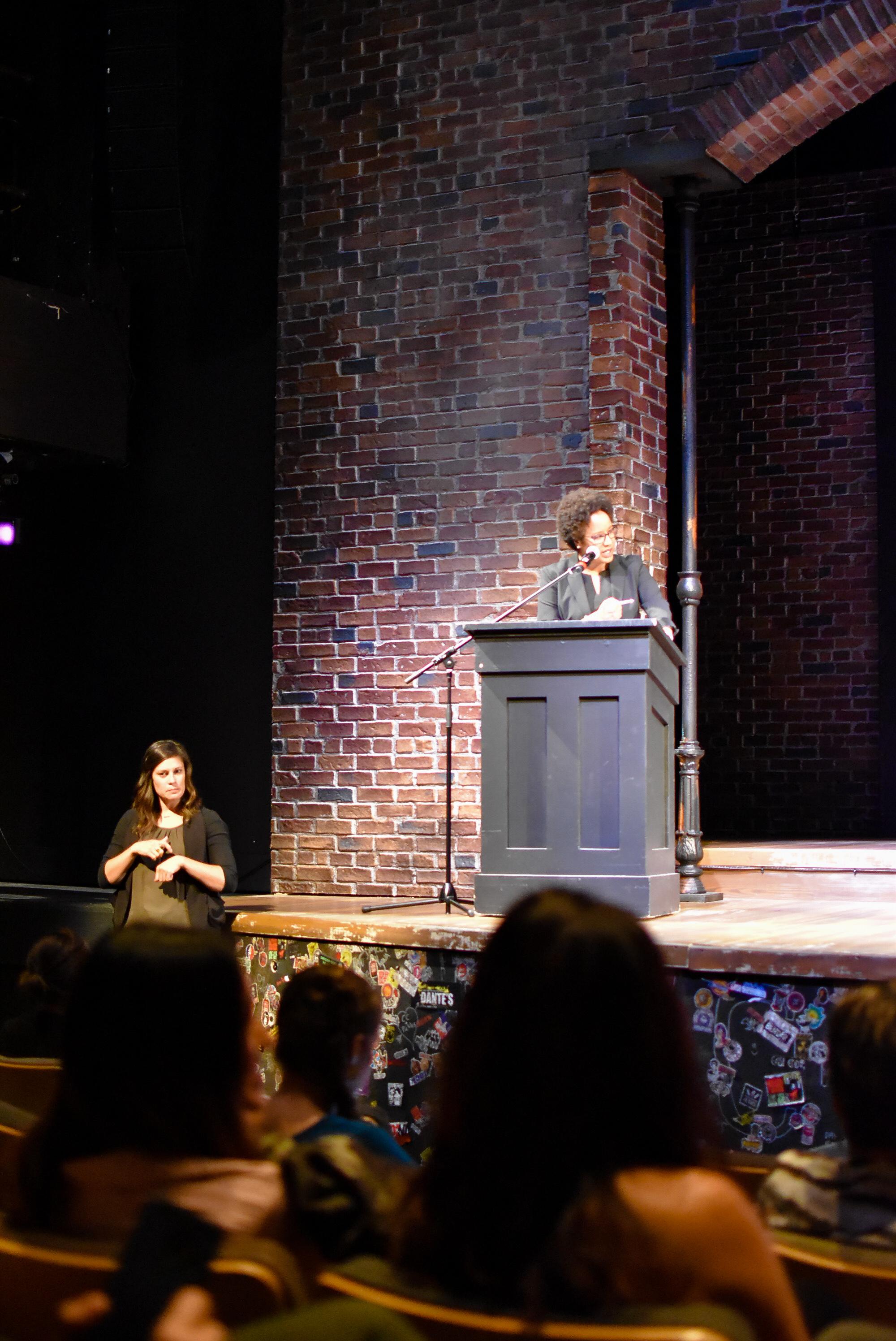 Dr-Harriet-Nembhard on stage addressing the speaker panel.JPG