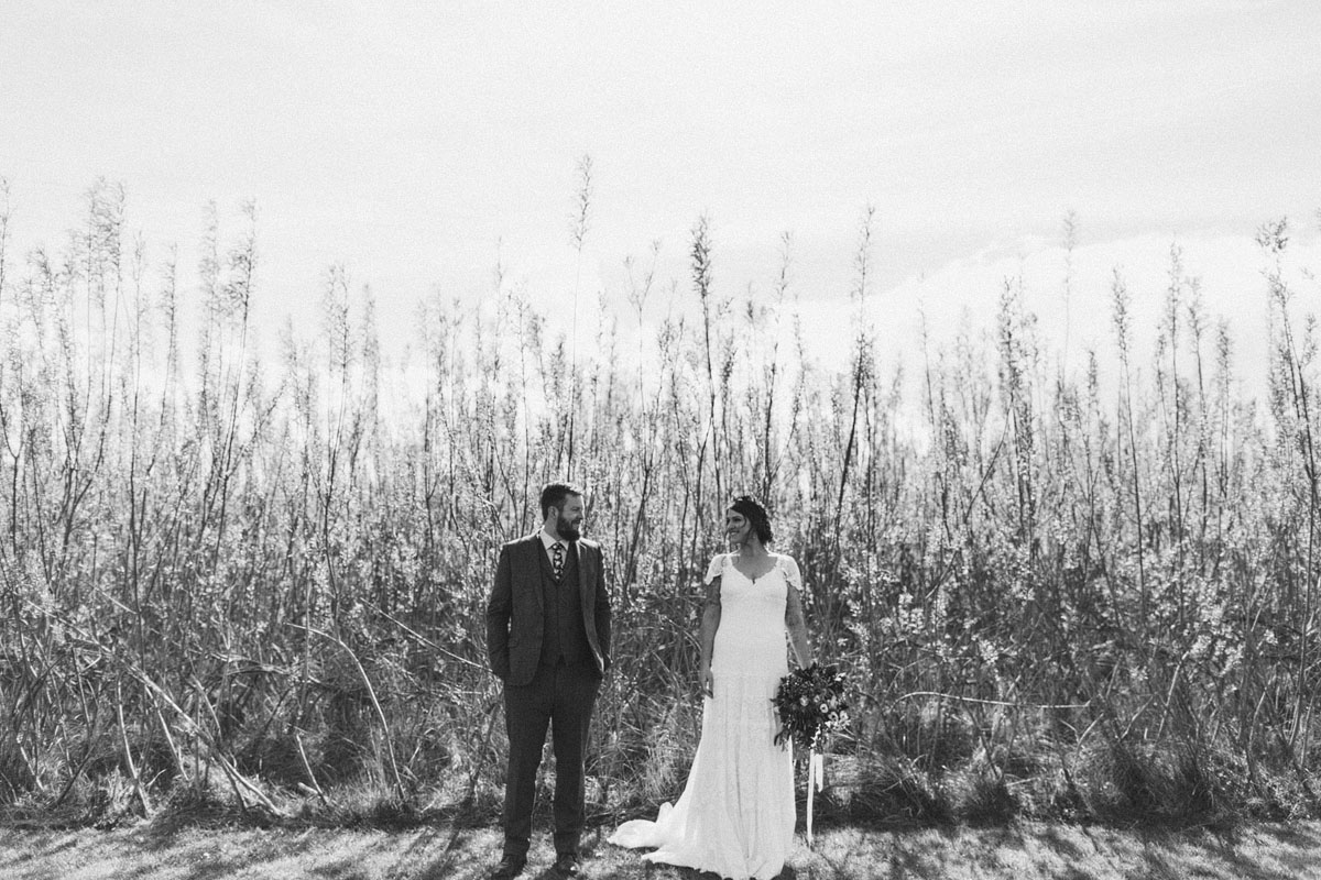 black and white wedding photo bride in white dress looking at groom lovingly tall grass in the background