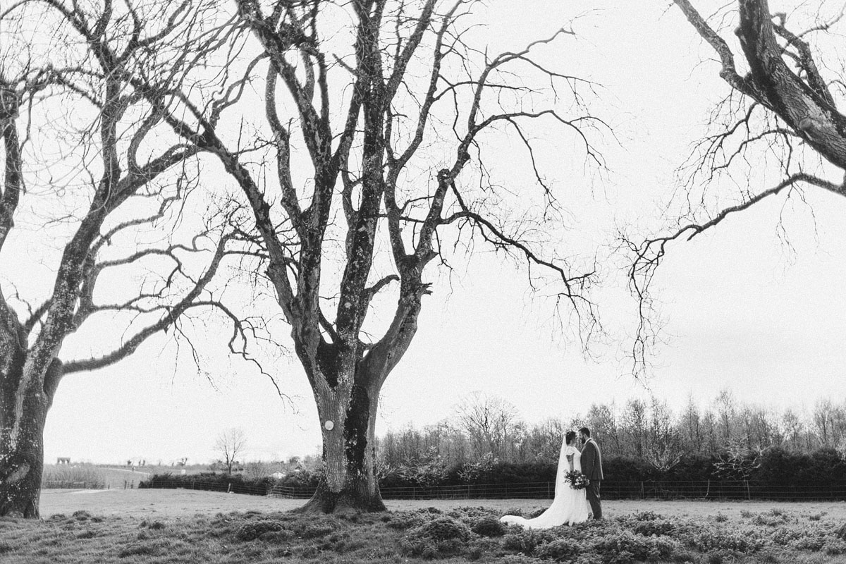 black and white photo bride and groom kissing surrounded by trees open space