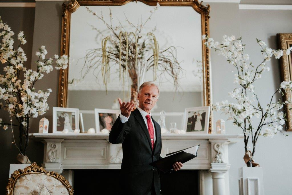 billy hutchinson humanist wedding celebrant officiating a ceremony gesturing with hand to guests in a living room style setting