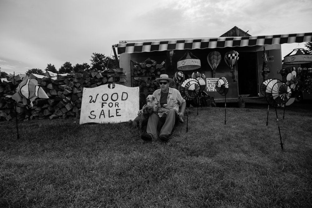 "Al Bush, who travels from location to location via motorhome with his wife and pets sits for a portrait on land he occupies with permission from a friend during the annual ""50 Mile Yard Sale"", Saturday, July 20, 2016 along Route 90 in the Cayuga Lake region of the Finger Lakes, New York."