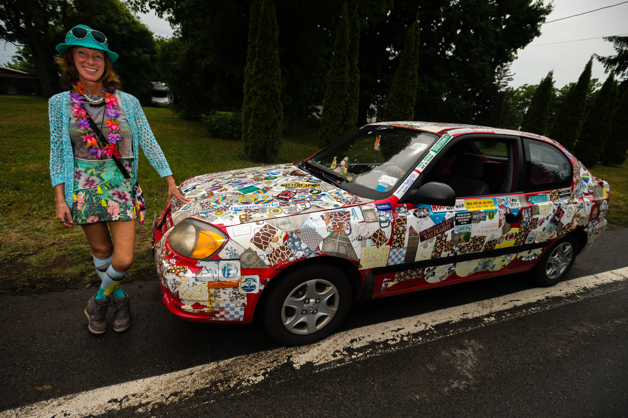 "Jesse Klein, a resident of Auburn, stands next to her third vehicle owned and adorned with a myriad of stickers during the annual ""50 Mile Yard Sale"", Saturday, July 20, 2016 along Route 90 in the Cayuga Lake region of the Finger Lakes, New York. Klein travels to the annual event which she refers to as her ""yearly weekend vacation"" as an opportunity to shop for objects and materials to repurpose into functional art."