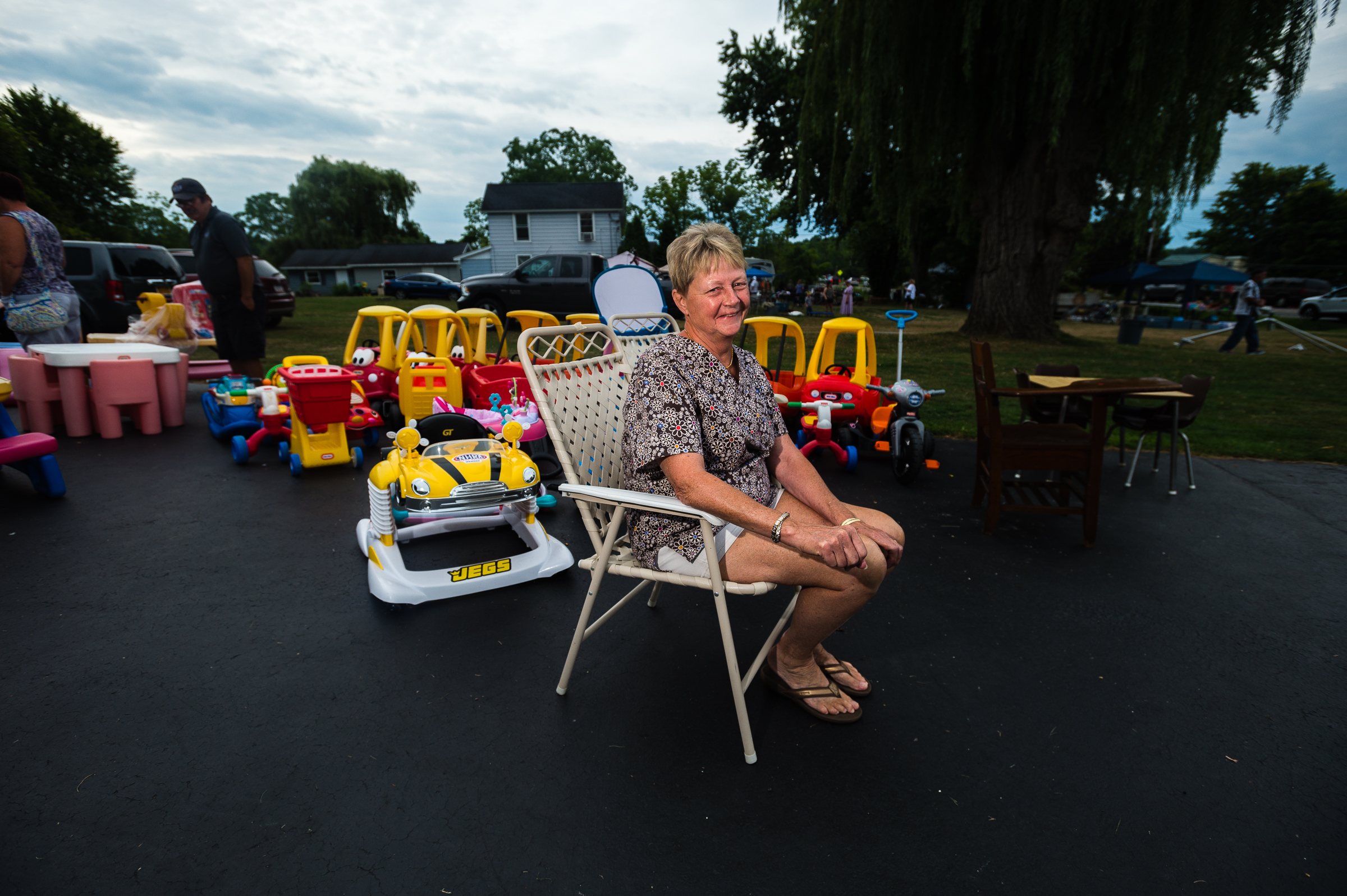 "Village of Cayuga resident Sandy Ehrlich sits in her driveway for a portrait among children's toys during the annual ""50 Mile Yard Sale"", Saturday, July 20, 2016 along Route 90 in the Cayuga Lake region of the Finger Lakes, New York."