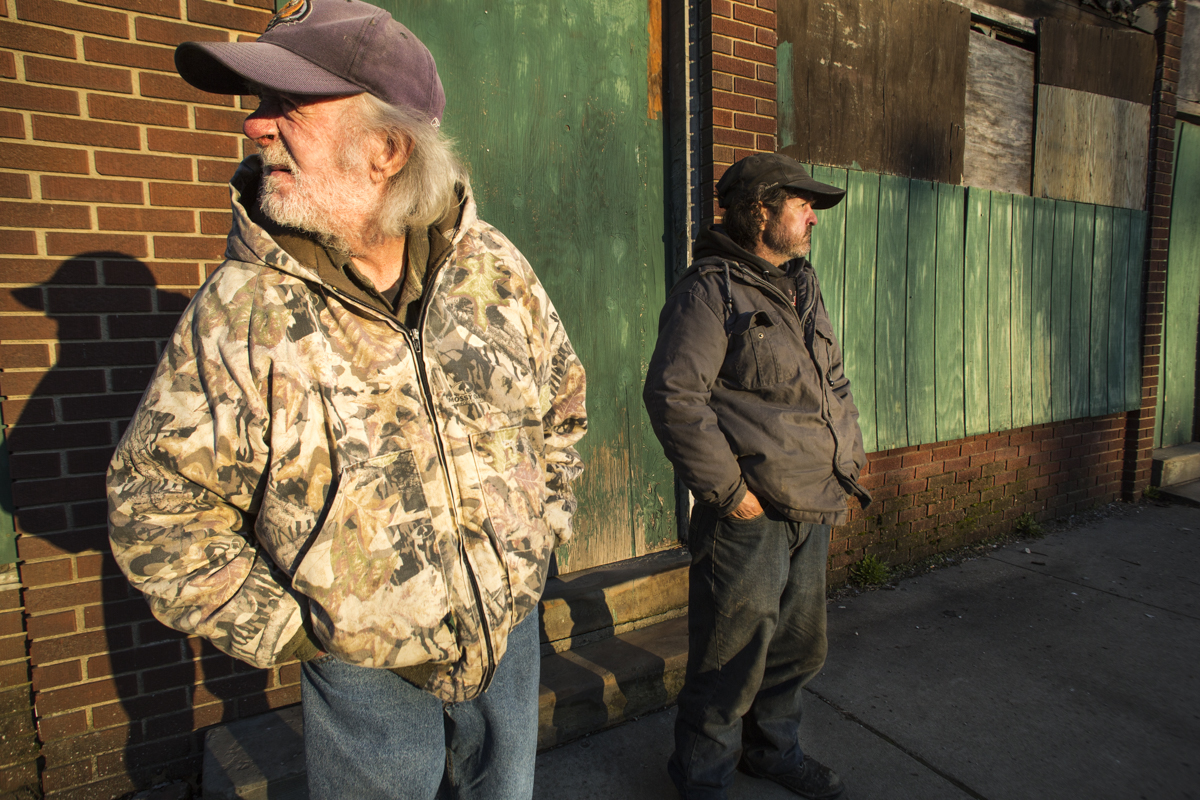 James Reed, left, and John Exline pass the time watching cars go by outside of the former Wonder Bar on Glouster's main street. Exline says he is unable to find work in Glouster, and is unable to drive because of recent seizures. He survives on Food Stamps and the occasional extra money from his sister who lives in Jacksonville, Ohio.