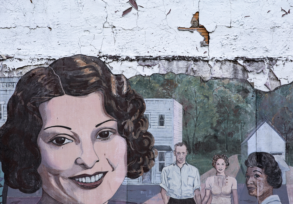 "Mural of Glouster that overlooks where the old hotel used to be. A mural is attached to the side of the former Gene Rushing's Tire Shop. Mayor Miles Wolf says each of the persons portrayed is ""someone who did something great in town."" On the left is a portrait of Ida Mae Stoneburner who founded The Glouster Project and restored the Glouster train depot among other things."