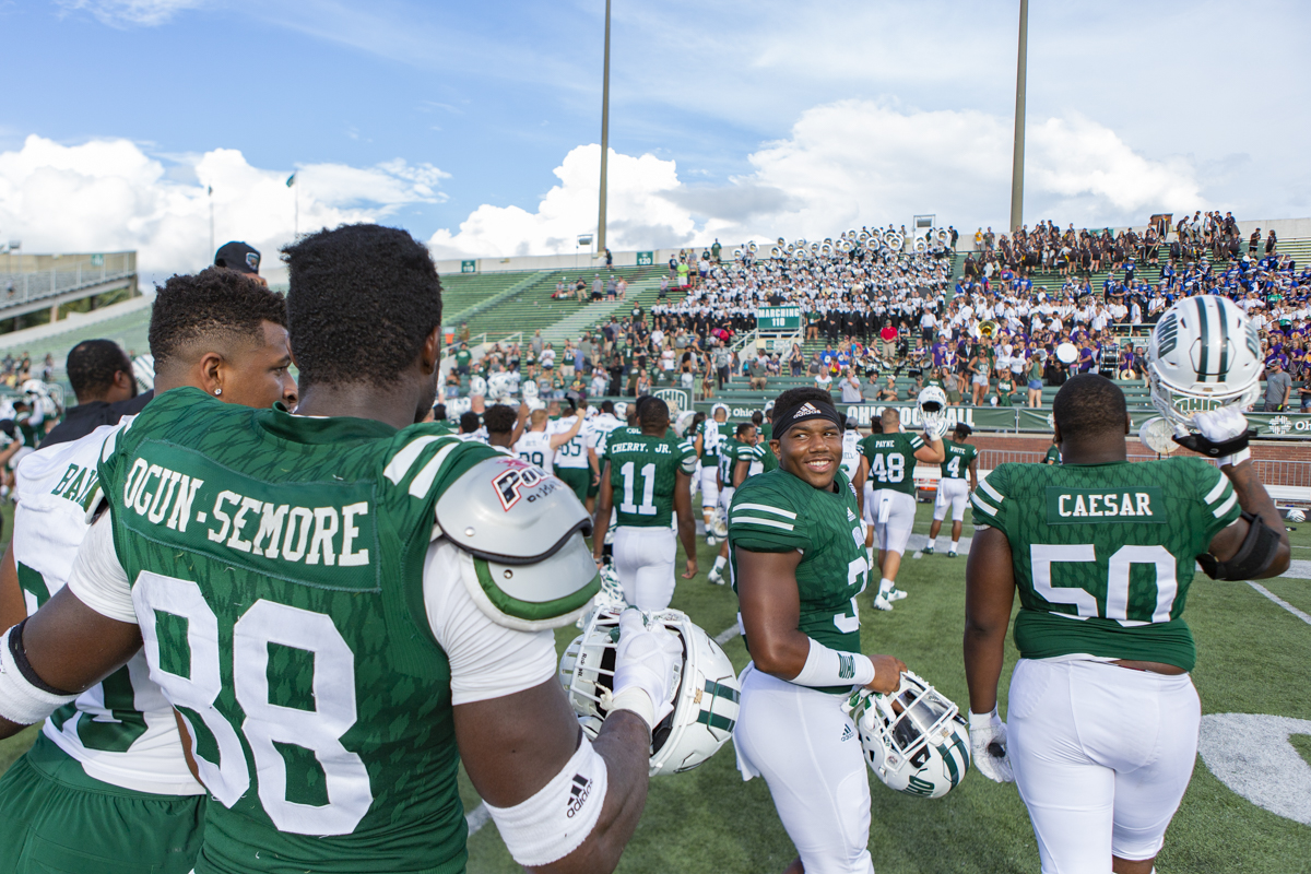 Ohio University players Amos Ogun-Semore, left to right, Bryce Houston, and Kaieem Caesar celebrate after the Bobcat's season opener, Saturday, September 1, 2018, at Peden Stadium.