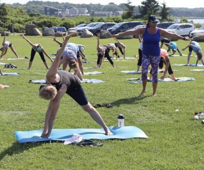 Hathaway leads the outdoor yoga session in 86 degree heat. Photo by: Kenneth Borges.