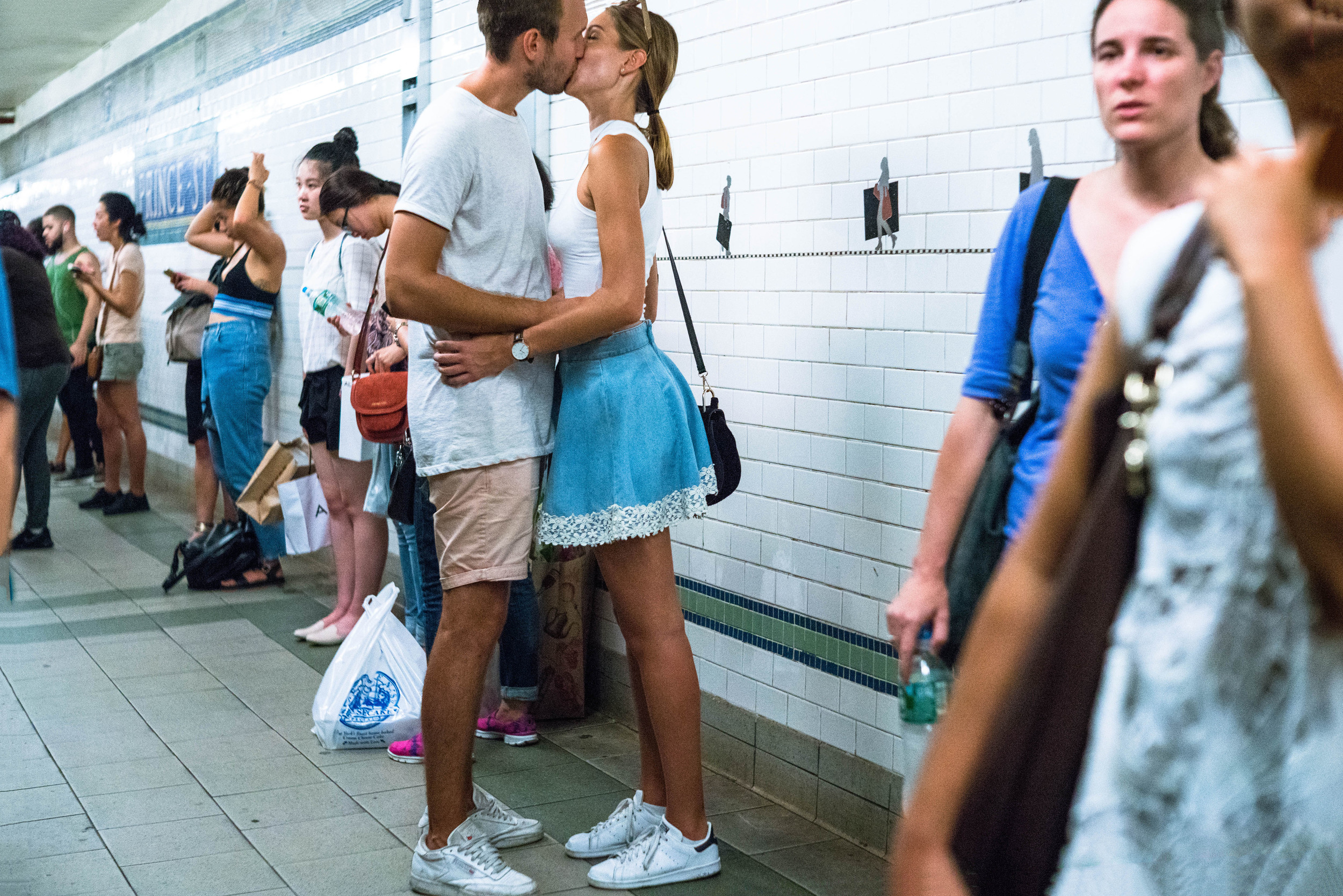 I shot this in the subway station, with no more room to back up to get the two subjects into the frame. I got her into the frame. Unfortunately, part of his head was outside the frame.