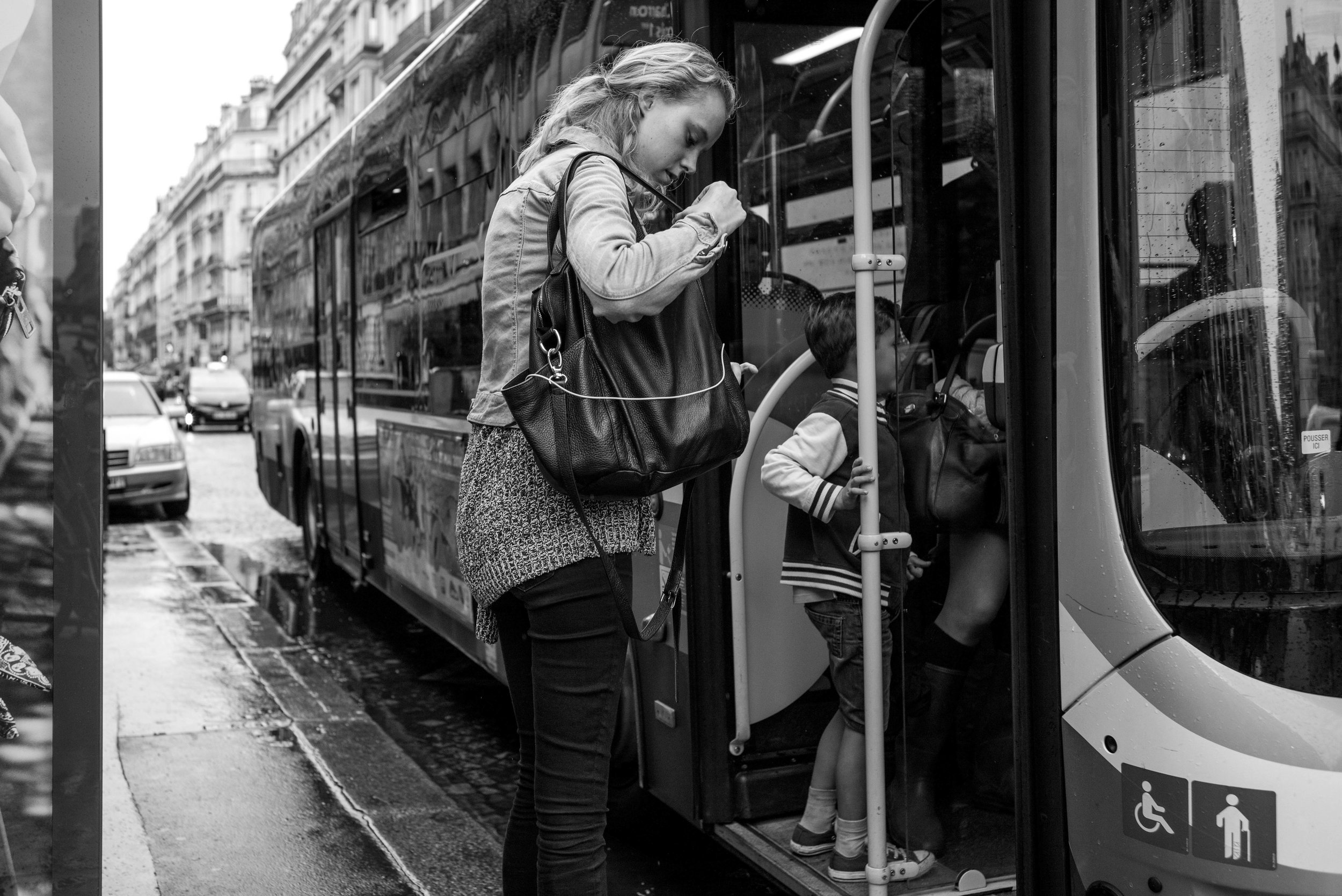 A woman getting onto a bus. Not exactly interesting. But since I was just standing around the bus stop, it was an easy photo opportunity. So I figure why not. Not exactly much thought was put into it.