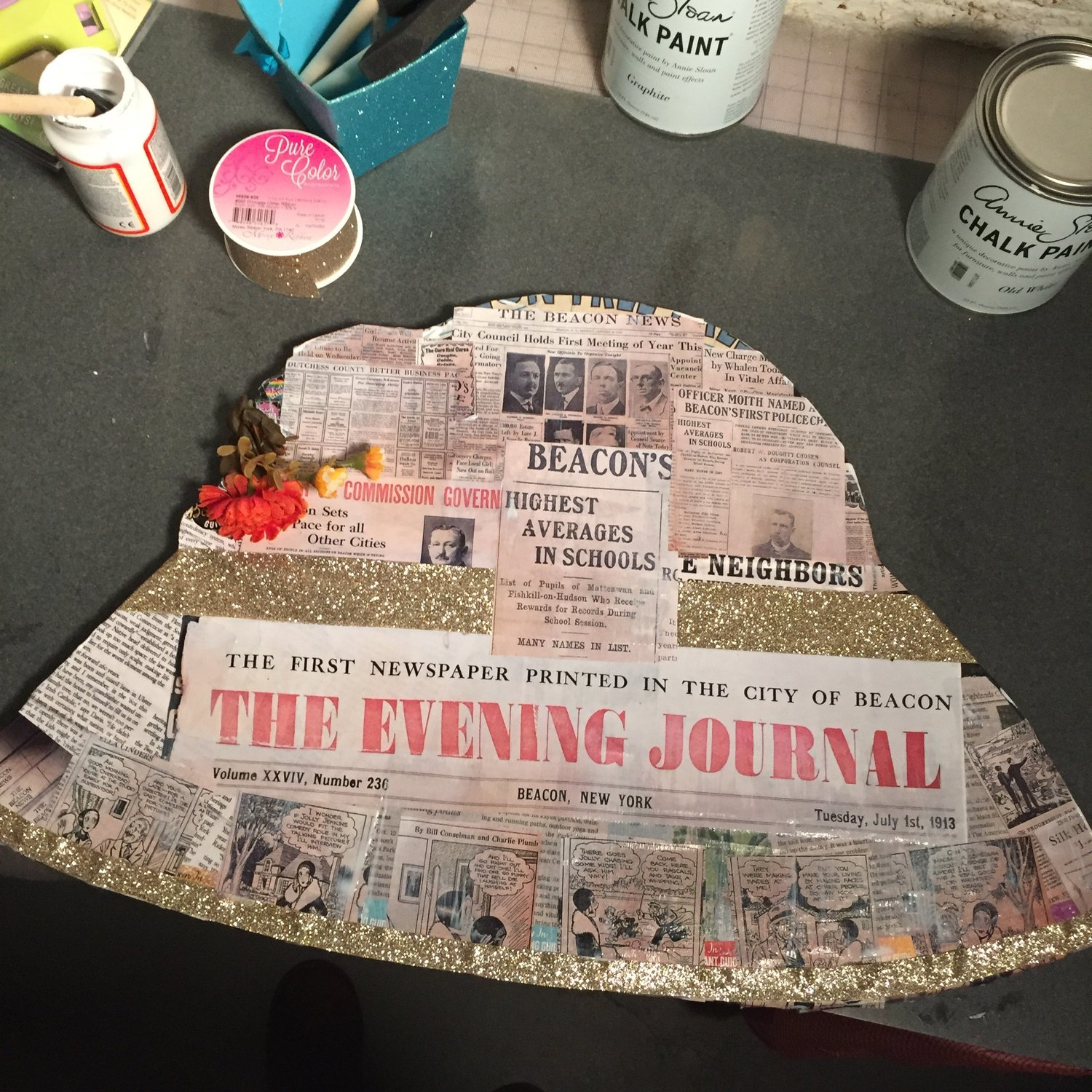 My own hat, a collage of newspaper articles from the first newspaper printed in Beacon in 1913, and clips from 1930s editions of The Beacon News. Clips were photographed from the Beacon Historical Society's collection of bound newspapers and color-printed at Accuprint, then glued onto the board.
