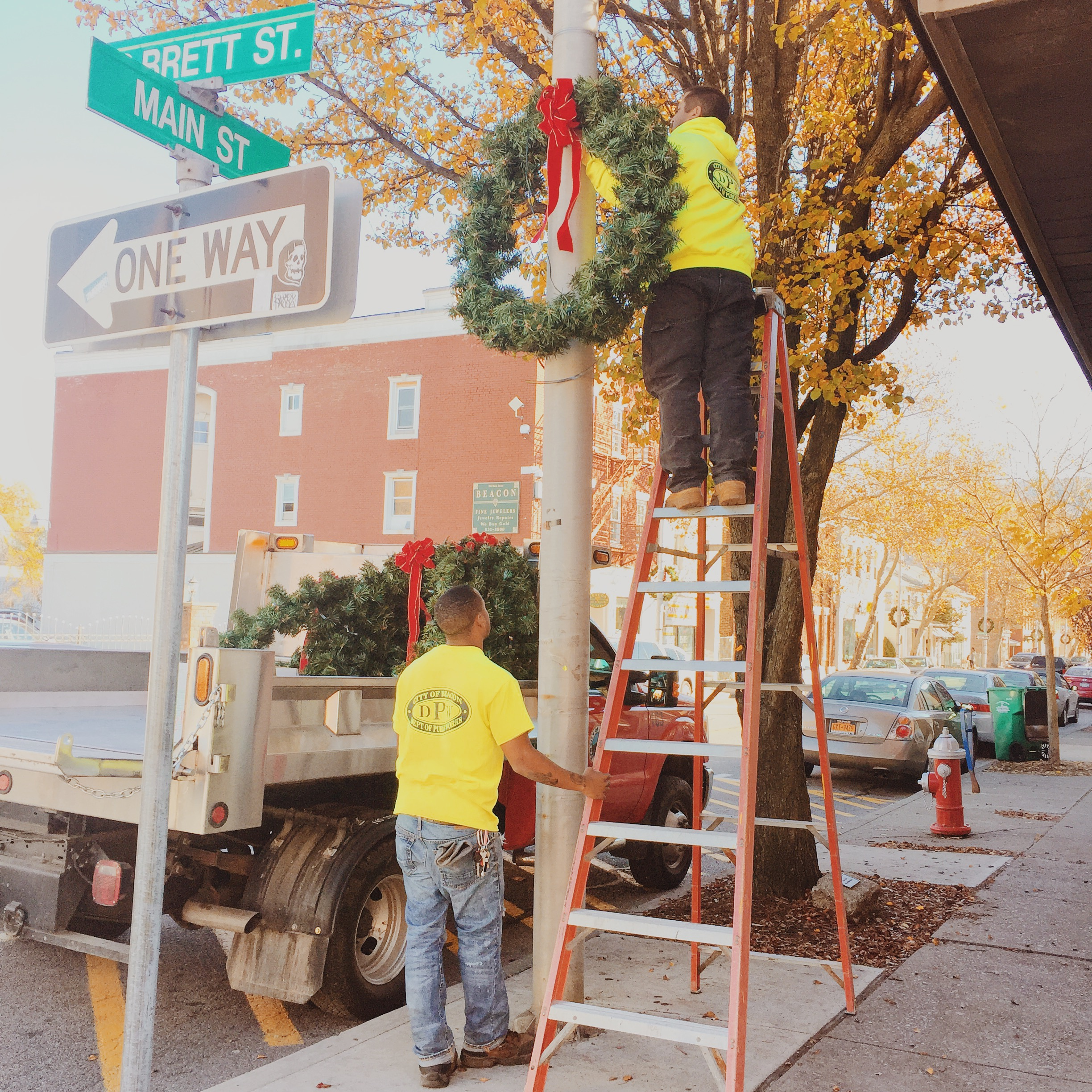 Highway Department staff working together to hang the wreaths.