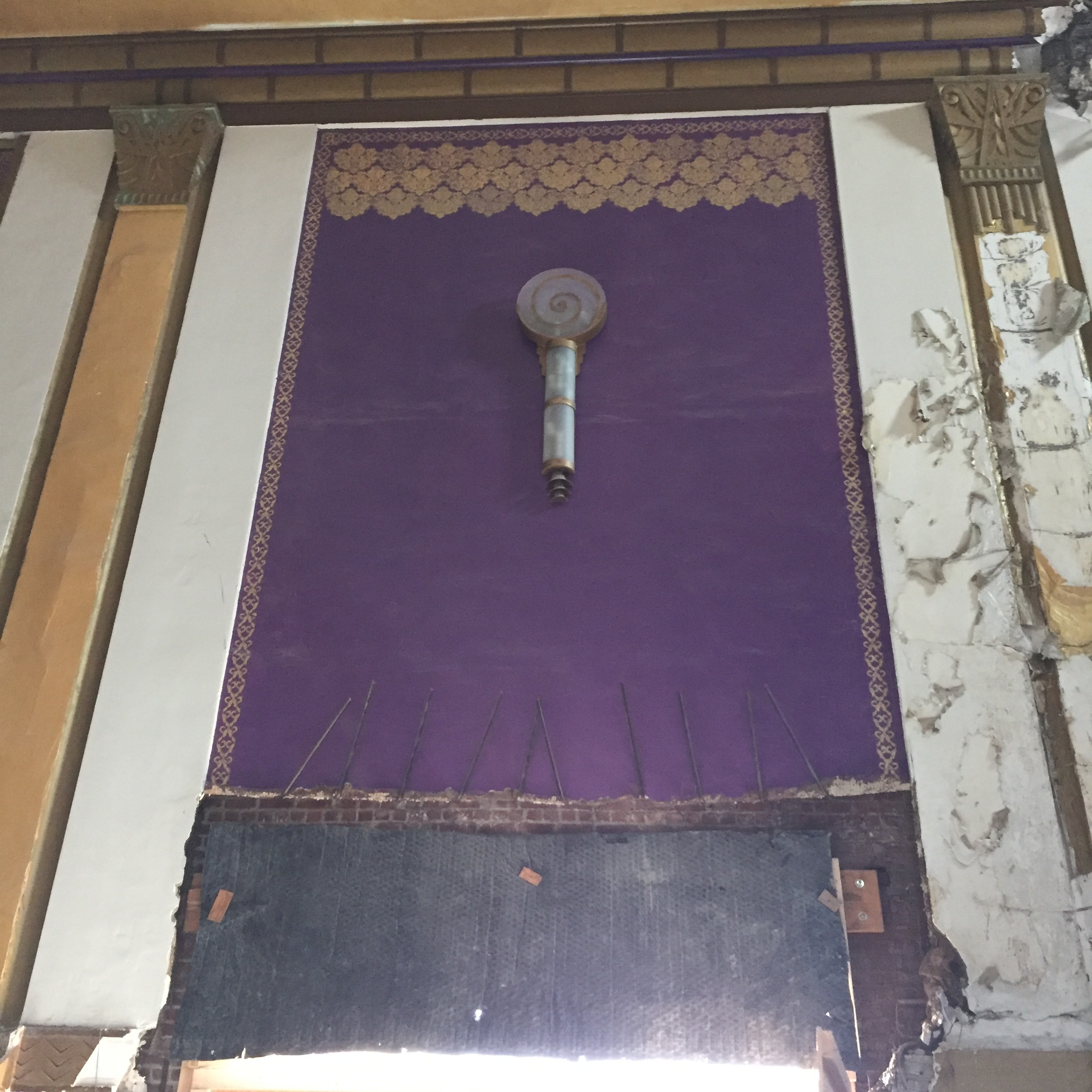 Old and older clash: Original sconces from the theater remain on the purple walls, which were painted by tenants running a church. they also installed purple chairs. Photo Credit: Katie Hellmuth Martin