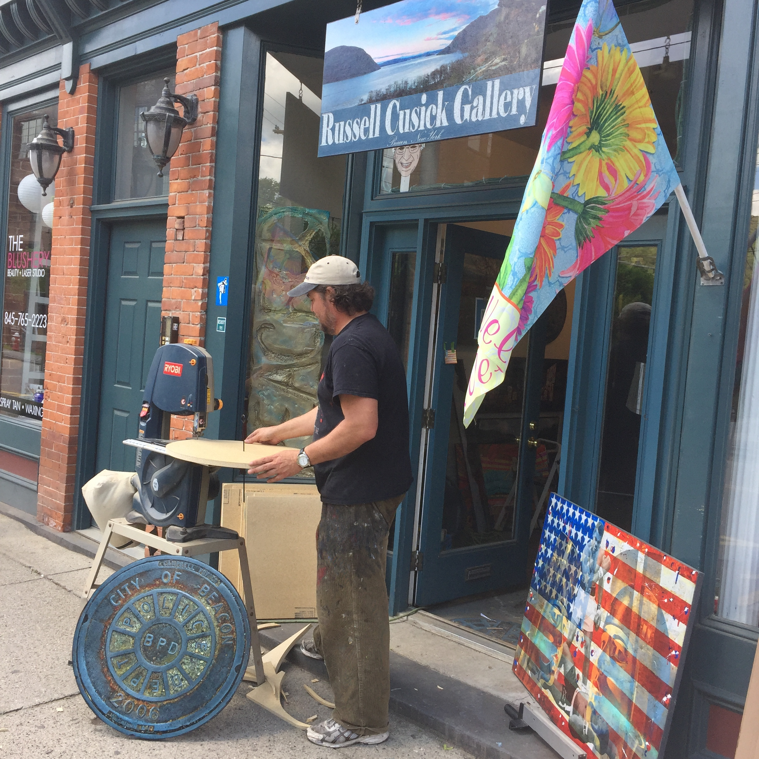 The artist Russell Cusick outside of his East End gallery, making one of his signature Beacon manhole covers.