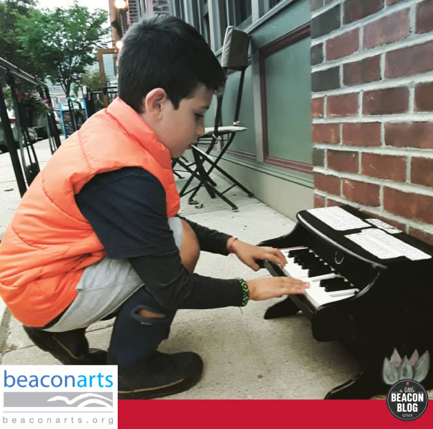 A boy crouches to play a tiny piano outside of Towne Crier. Photo Credit: Lisa Marie Martinez; Piano Artist:  Miss Vickie
