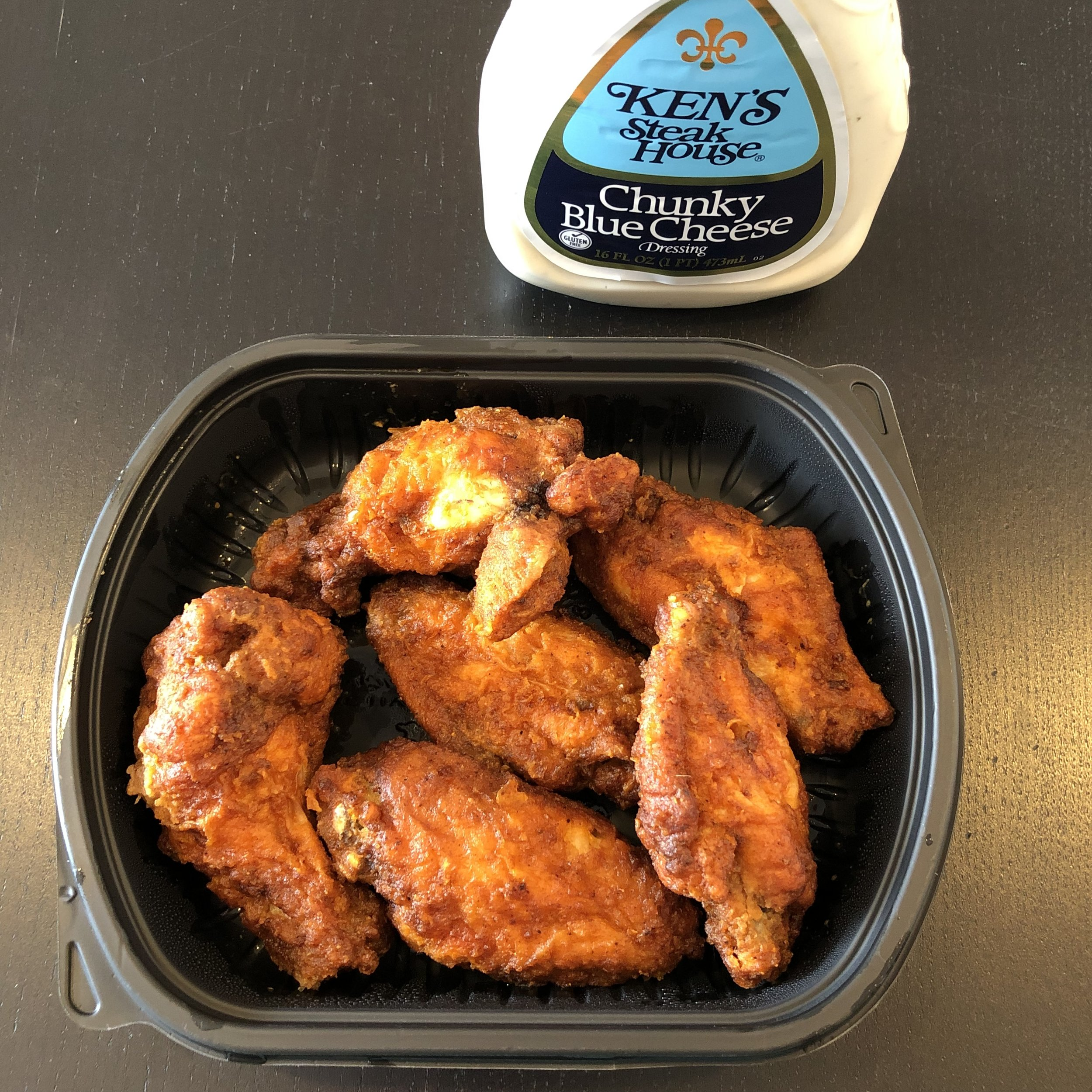 Buffalo wings at Key Food in their secret sauce. Blue cheese available on the shelf nearby.