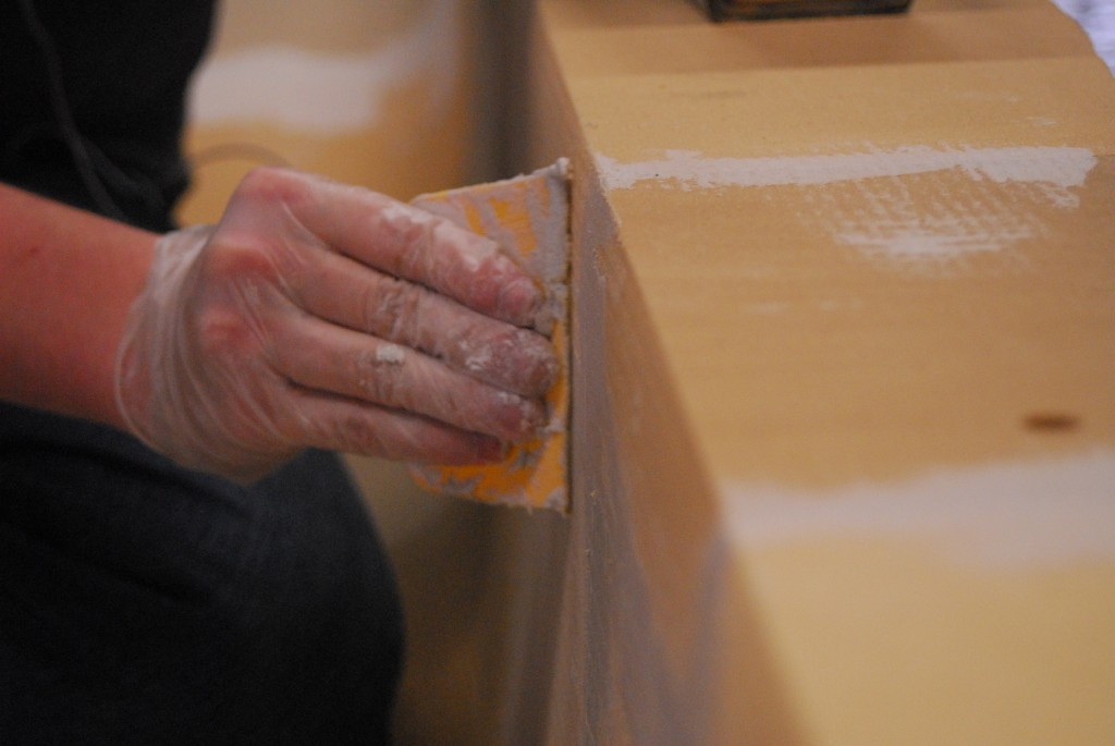 Close-up view of plastering the cracks between foam blocks in our mold.