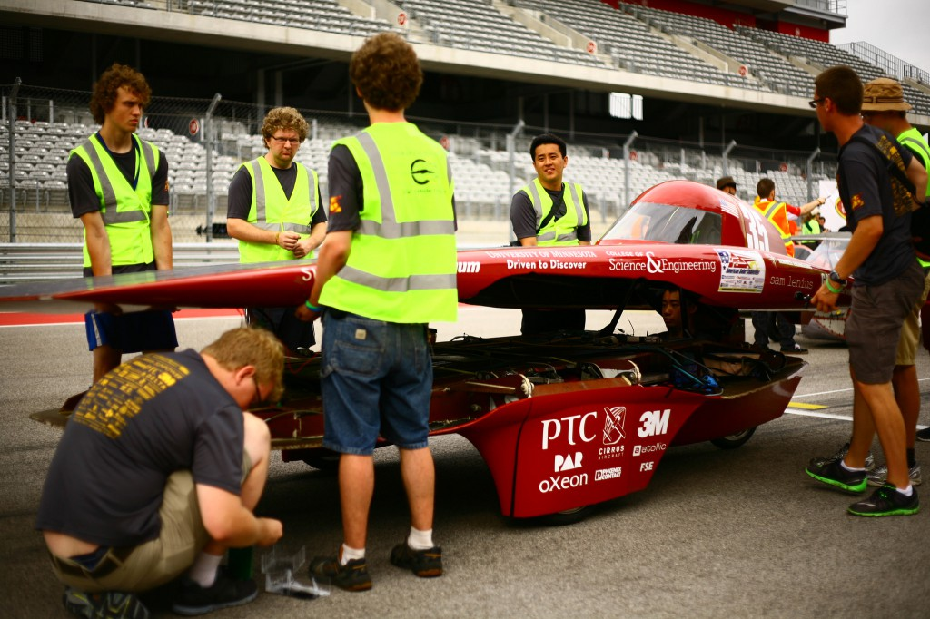 Electrical team members stand with the car before the start of the race on day 2.