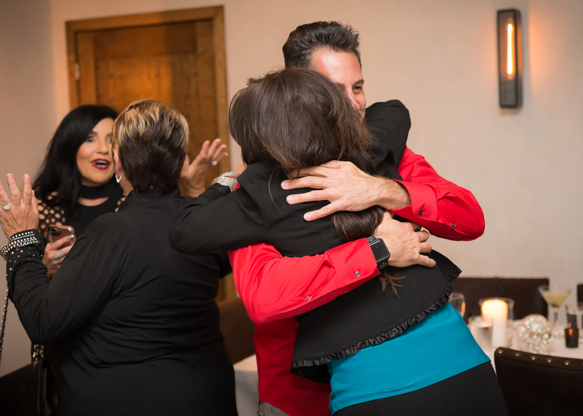 Friends and family hugging Chris
