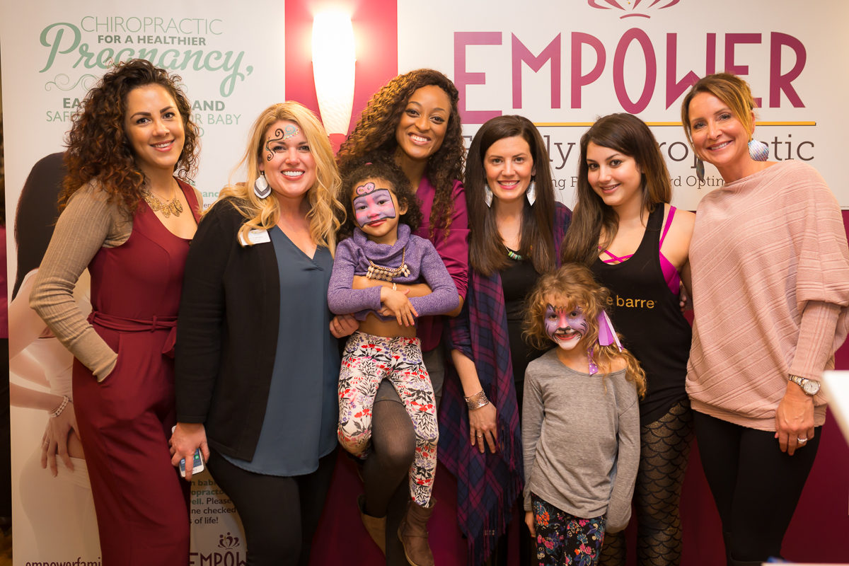 Jeannique Norbert (center) poses with friends during the Empower Family Chiropracticgrand opening