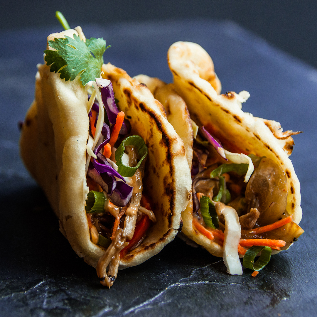 PULLED PORK NAANWICH (2)   Hand held naan bread sandwiches filled with slow cooked pulled pork in an asian bbq sauce, Sriracha aioli, Asian slaw, fresh cilantro & green onion.