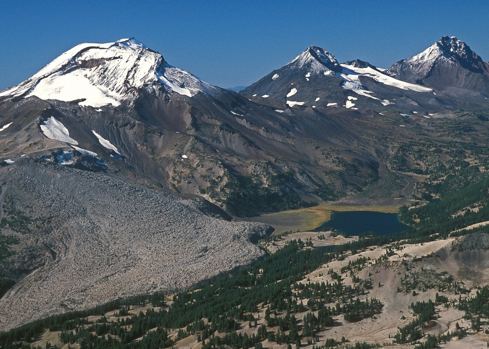The Three Sisters, individually known today as South Sister, Middle Sister and North Sister,and in early days as Faith, Hope and Charity. The 283,630-acre Three Sisters Wilderness is still a unit of the National Wilderness Preservation System, but is no longer a unit of the World Network of Biosphere Reserves.  Image: USDA Forest Service