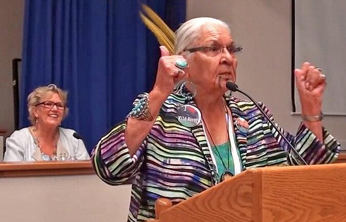 Fig. 1.  Mary Gautreaux (left) enjoying the remarks of Takilma elder Grandma Agness Pilgrim at a public meeting in Grants Pass . Source:  KalmiopsisRivers.org .