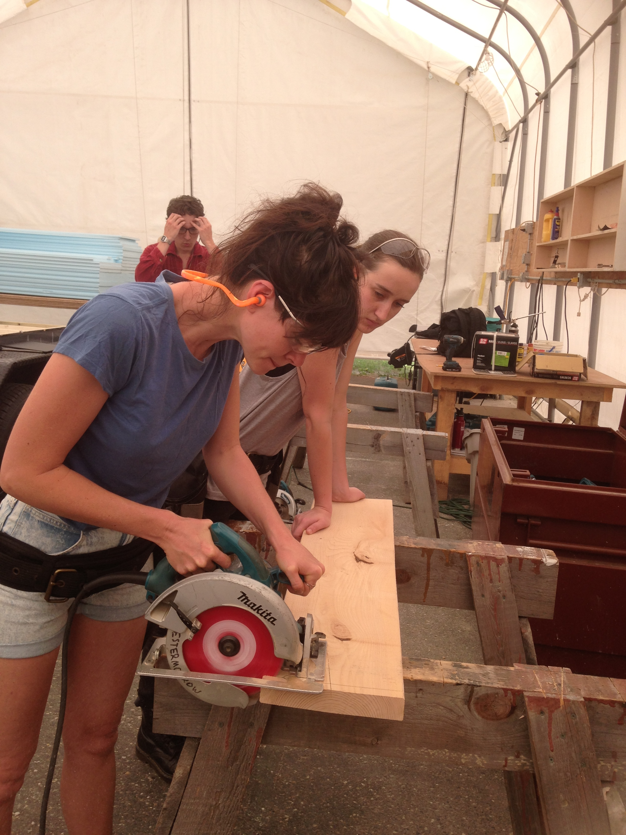 Lauren practices cutting with the circular saw while Tori looks on (and holds the board steady!)