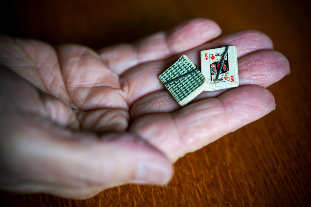 Two sets of miniature playing cards hooked together with a staple.