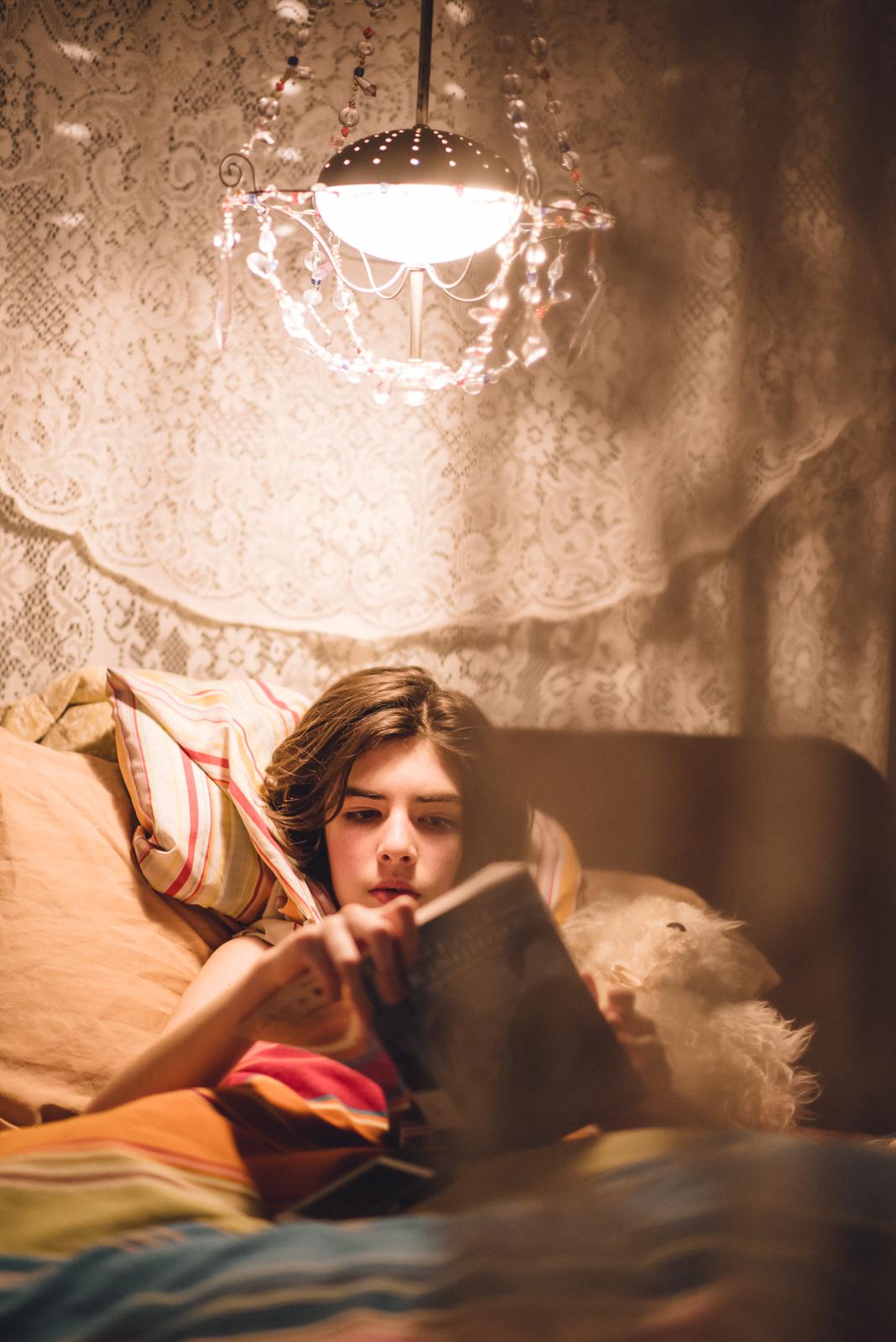 reading under a chandelier