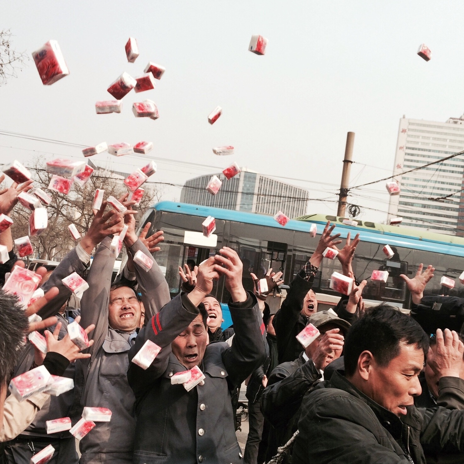 Factory workers scramble to catch free paper napkins thrown from a stage during a promotional event. Zhengzhou.