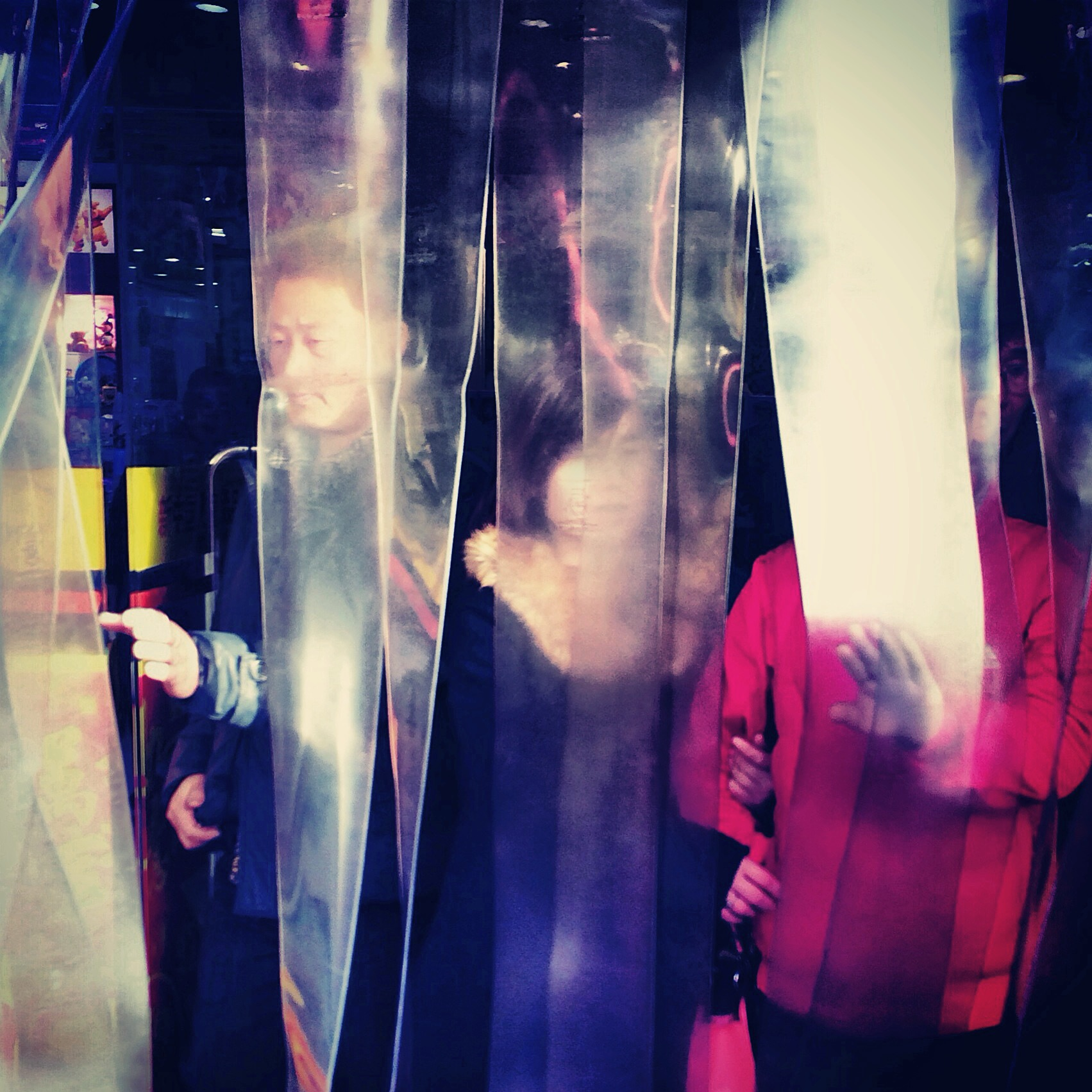 People exiting a shopping centre through plastic wind curtains, Beijing.