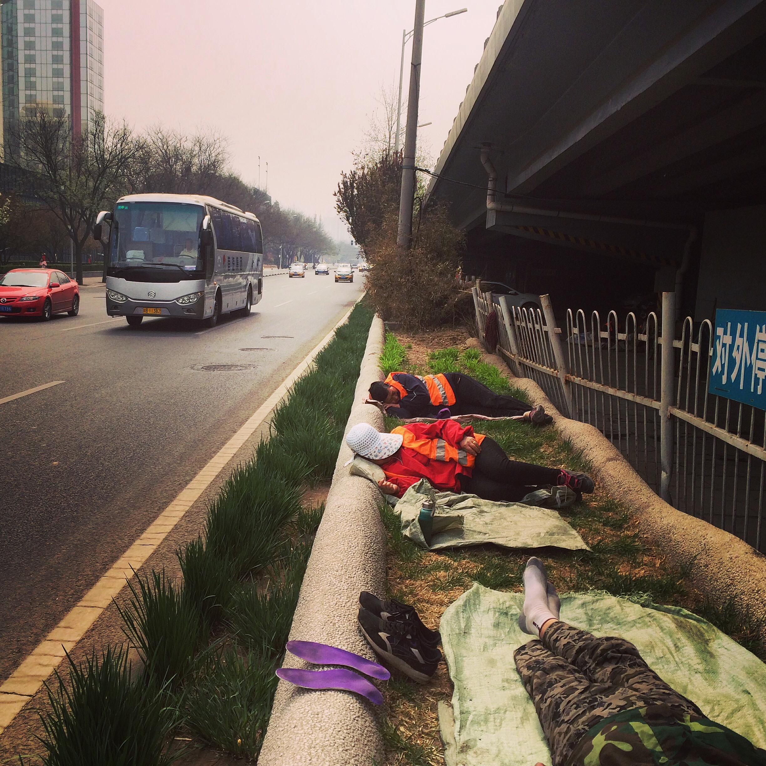Street sweepers take a nap beside the Third Ring Road, Beijing.