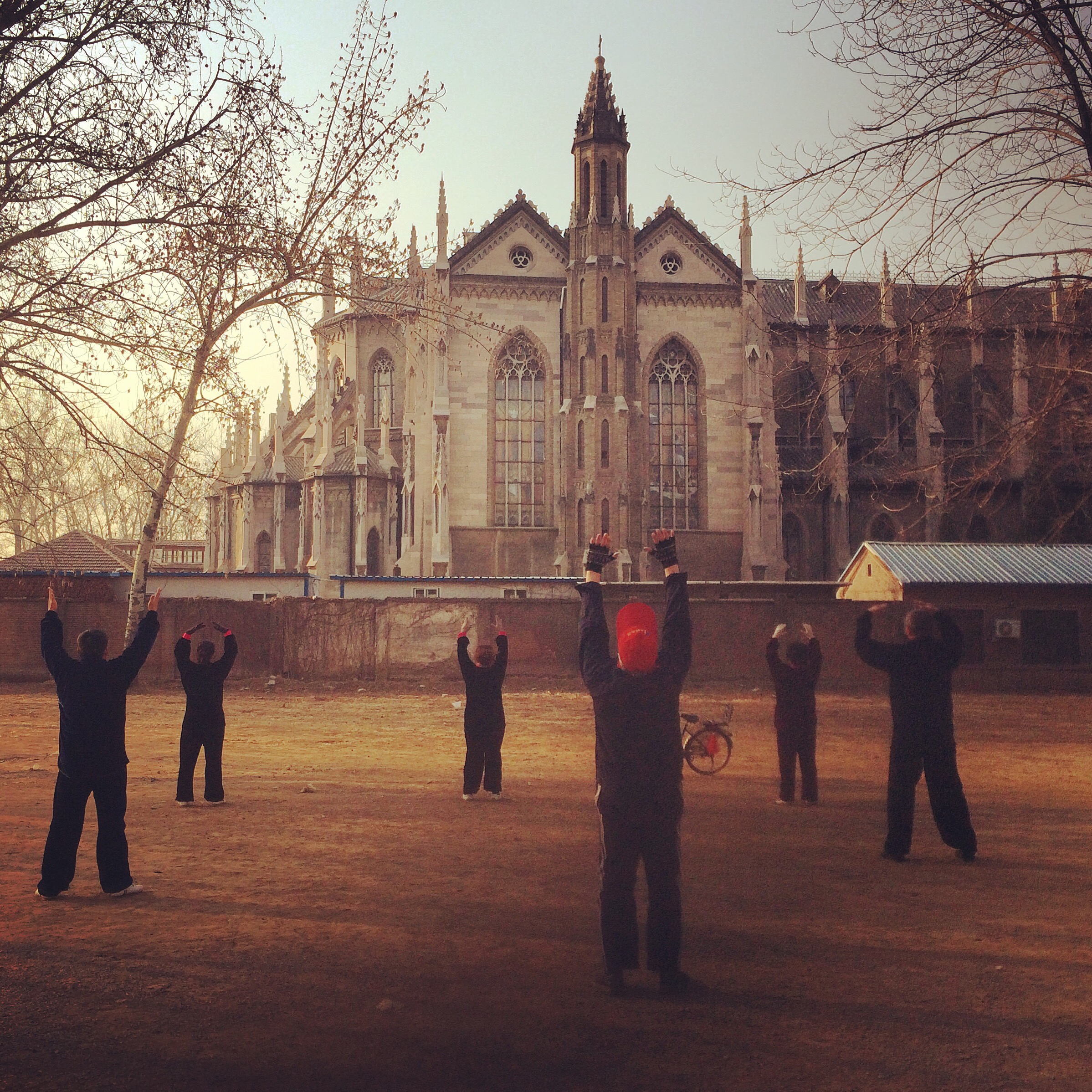 Elderly Chinese practice taiqi outside an old Catholic church, Jinan.