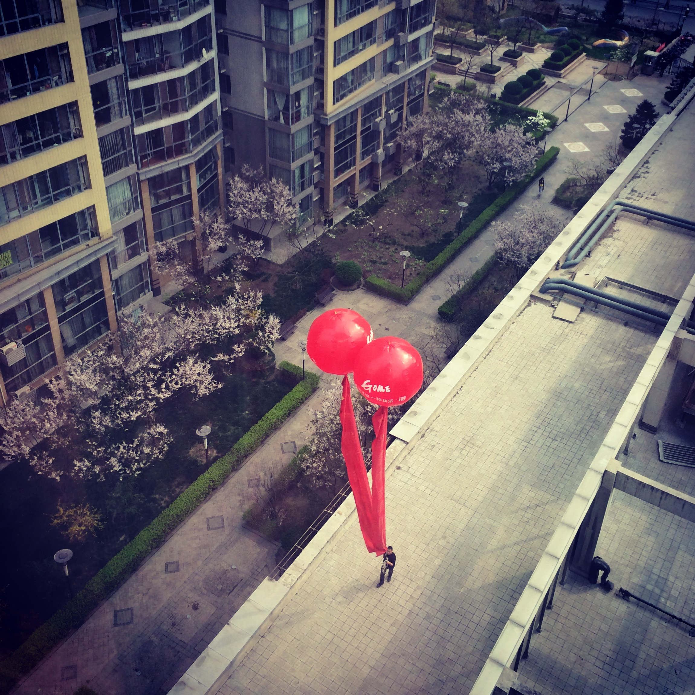 A man carrying giant balloons advertising a supermarket, Beijing.