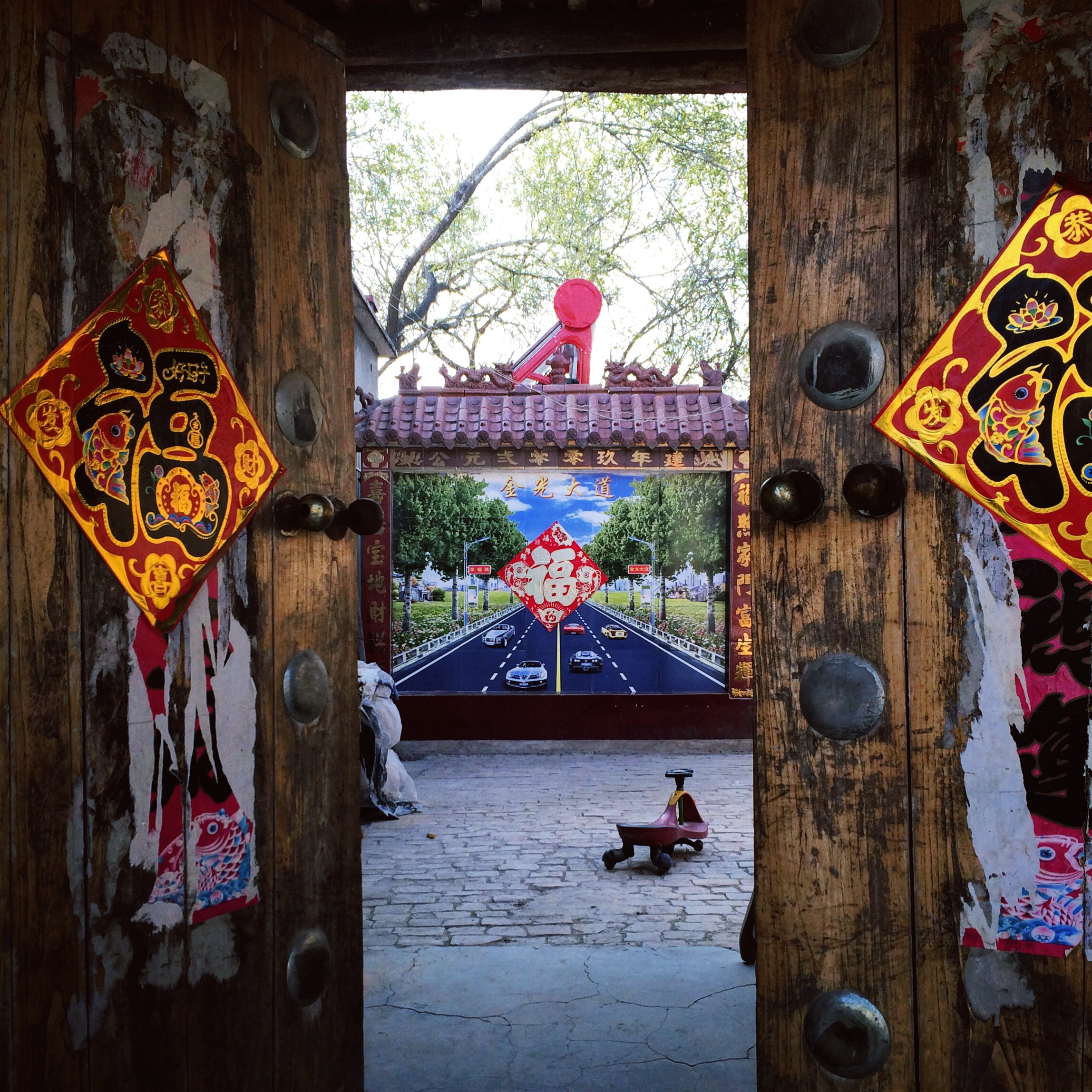 "A ""ghost gate"", meant to keep evil spirits from entering homes, decorated with a picture of modernity. Henan Province."
