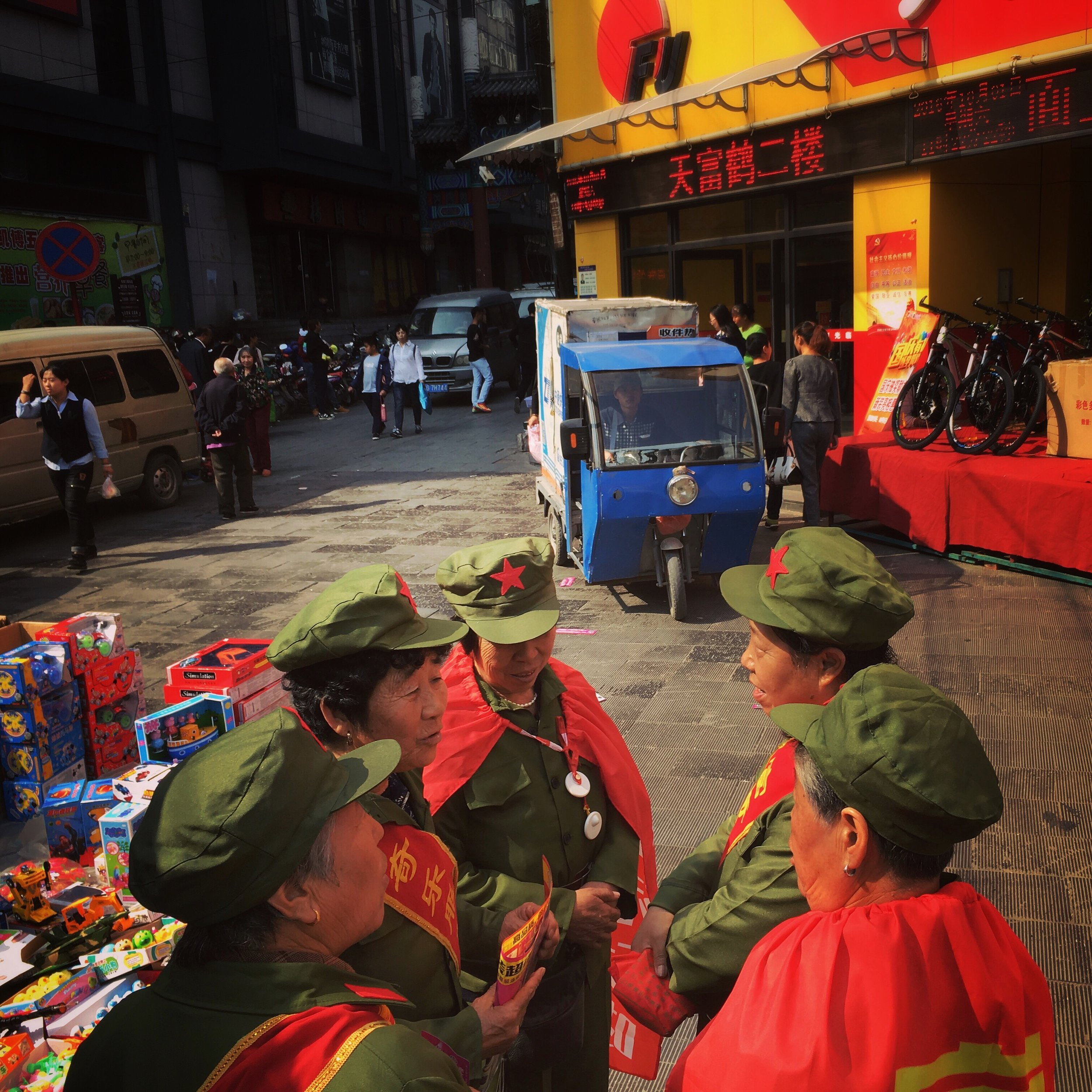 Old ladies dressed as Red Guards strategise before handing out promotional flyers for a supermarket. Zhangjiakou.