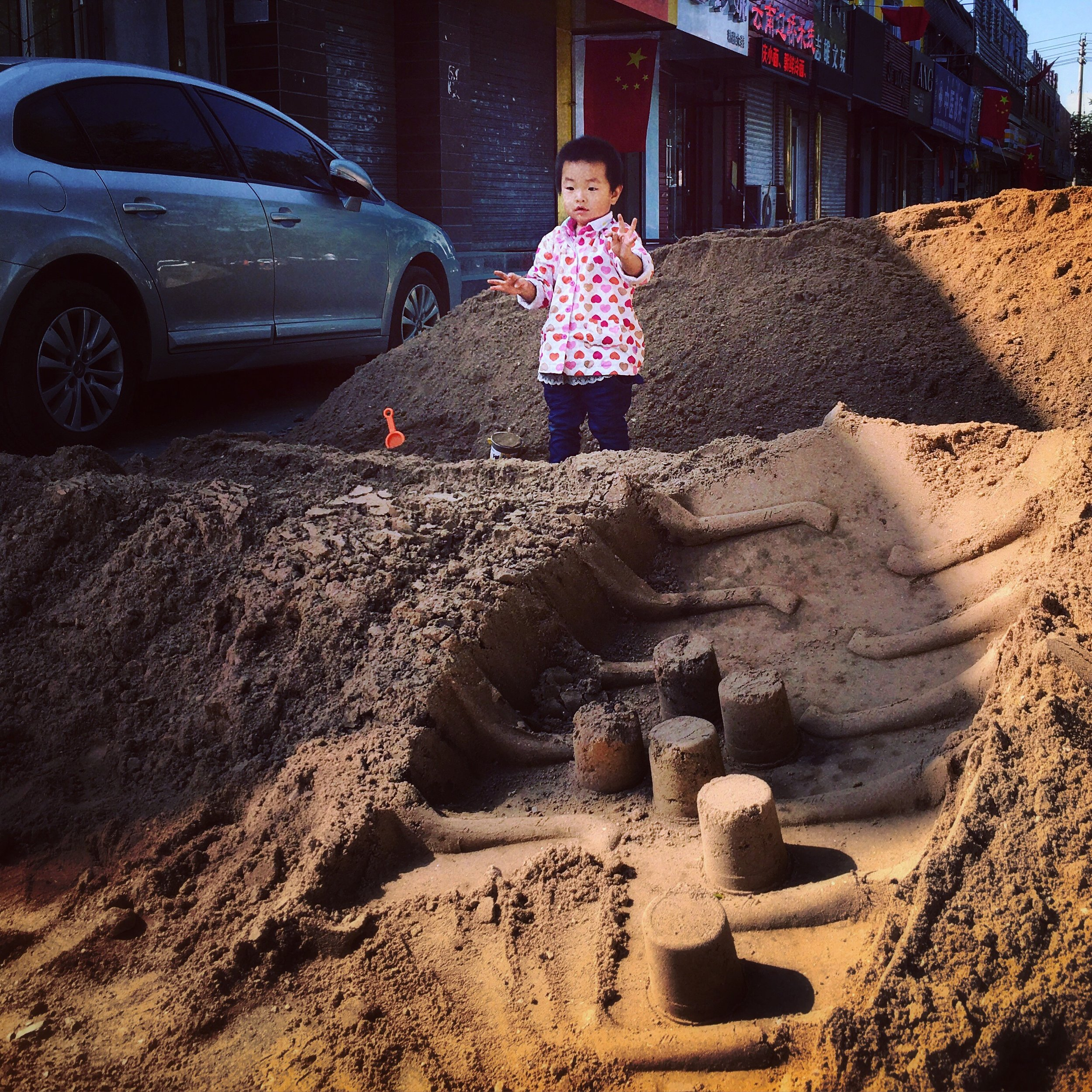 A little girl builds sand castles in the tire tracks of a construction site. Hohhot.
