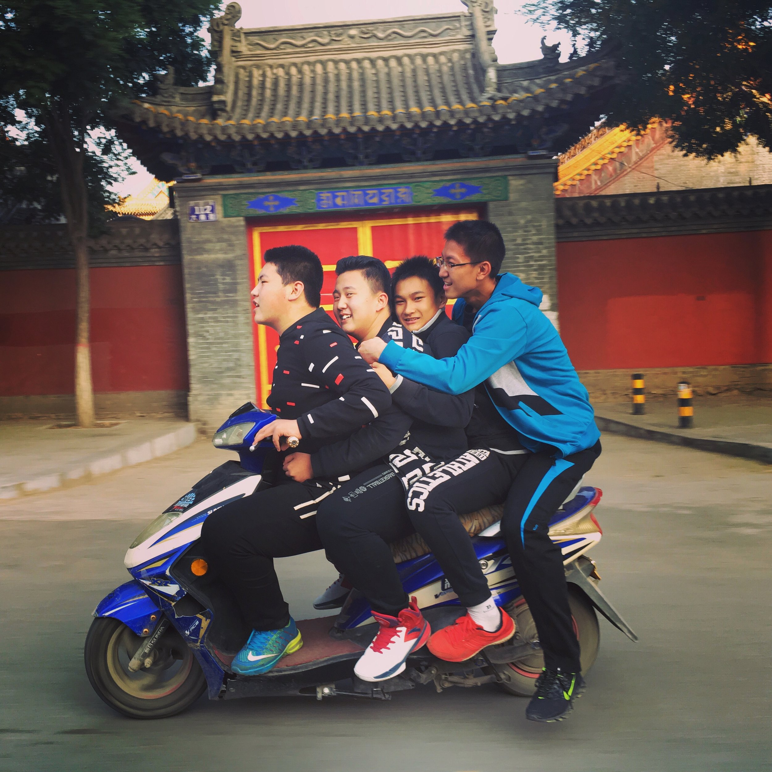 Four boys ride a motorbike in Hohhot, Inner Mongolia.