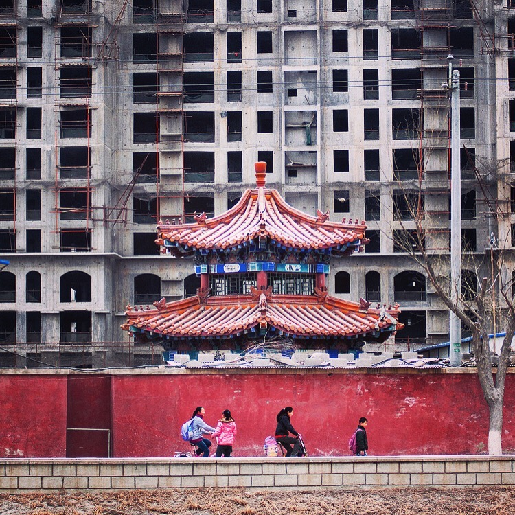 Kids pass an under construction apartment block on the way home from school in Lanzhou.