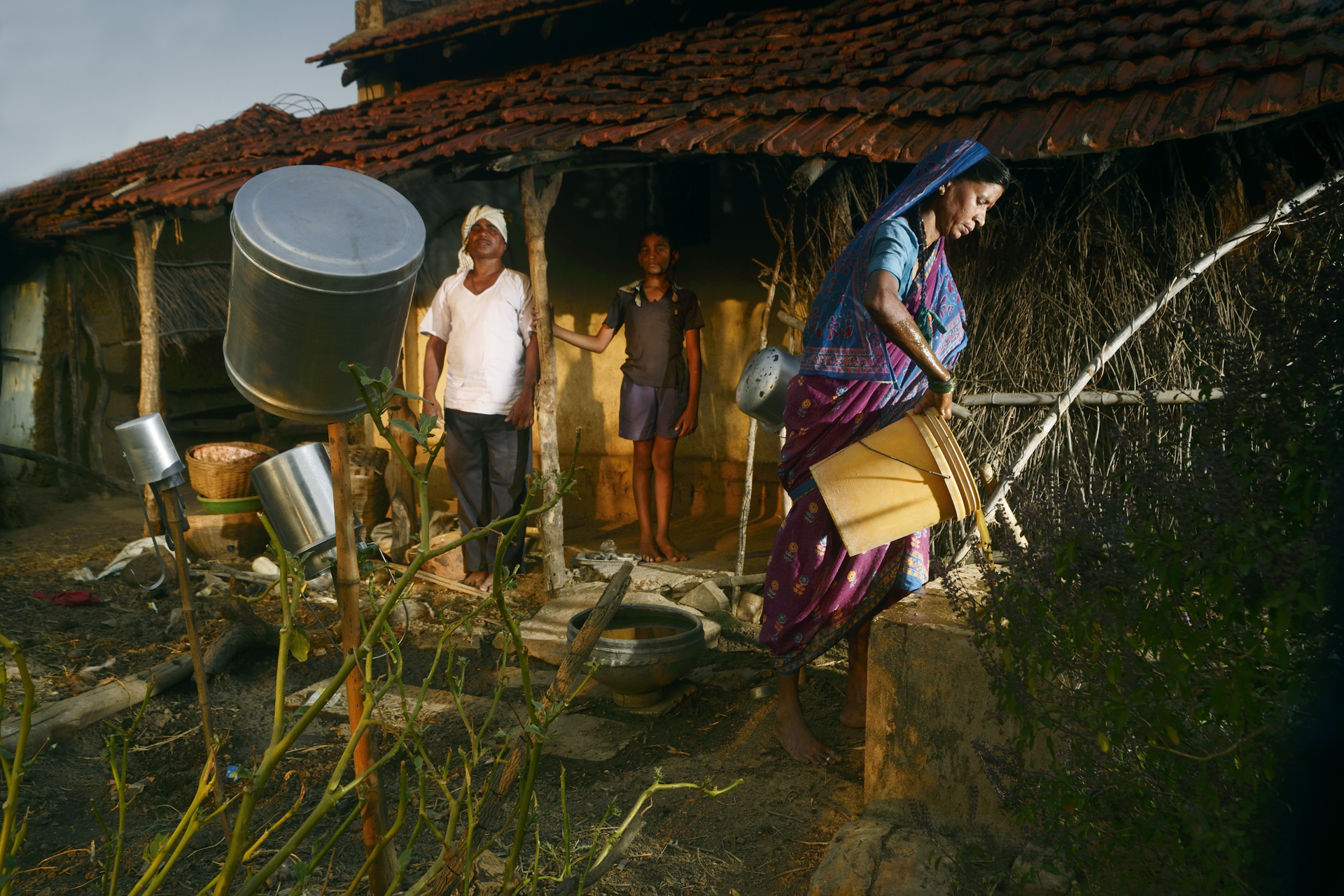 54-year-old Sarawan Tulsi Ram Wadankar   returns home in the evening. His wife pours cow dung into their biogas plant which meets their cooking gas requirements.