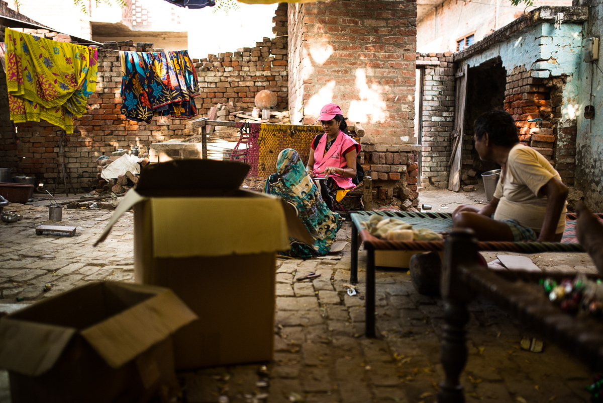 "October, 2016. Raina Village, Firozabad district, Uttar Pradesh, India.  ABT Associates Community Health Mobiliser Geeta Sharma spends time talking to Devkumari walking her through al the family planning options, and why she should opt for one of them. Dharam Veer, Devkumari's husband prepares glass moulded gift items for Christmas from his house in Raina village, Firozabad district, Uttar Pradesh, India. Devkumari and Dharam Veer have five children, four girls and one boy. She said, ""We wanted a boy so kept on trying until we had twins in our last delivery. One of them was a boy. We don't want anymore children. I want to opt for an injectible contraceptive option now"". The last twins they had are just over a year old now. ""We still havent used any contraceptive measure since the last delivery. That led to another pregnancy which we aborted by paying Rs 1200,"" confides Devkumari to a Community Health Mobiliser of ABT Associates during a one-one interaction. She acknowledges, ""If I had used an injectible earlier, it would have been cheaper than the abortion"". ABT Health Mobilisers had done a door to door visit earlier explaining family planning measures etc. but the couple didn't opt for any contraceptive option citing expenses."