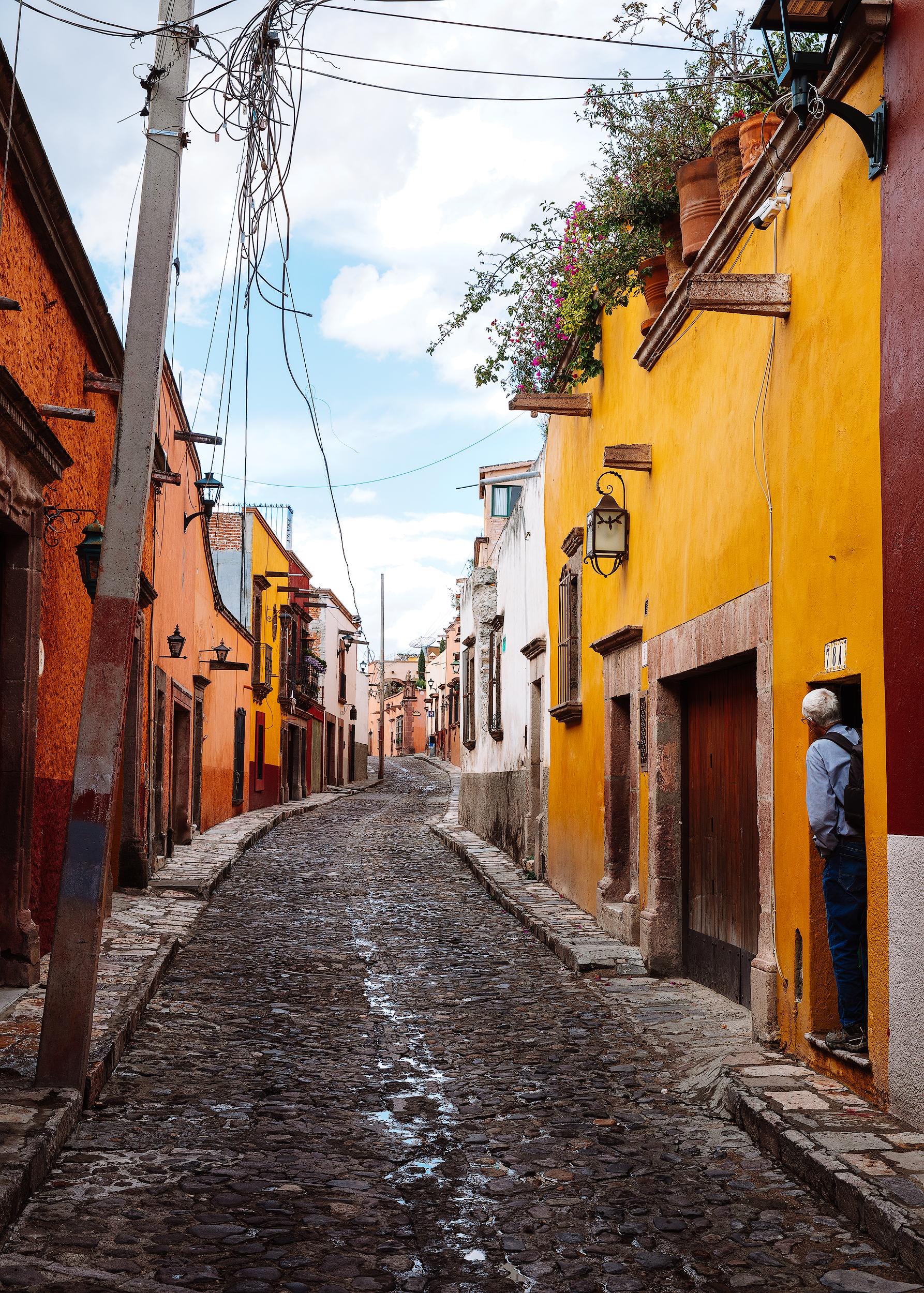 Man in doorway looking down the street in San Miguel de Allende