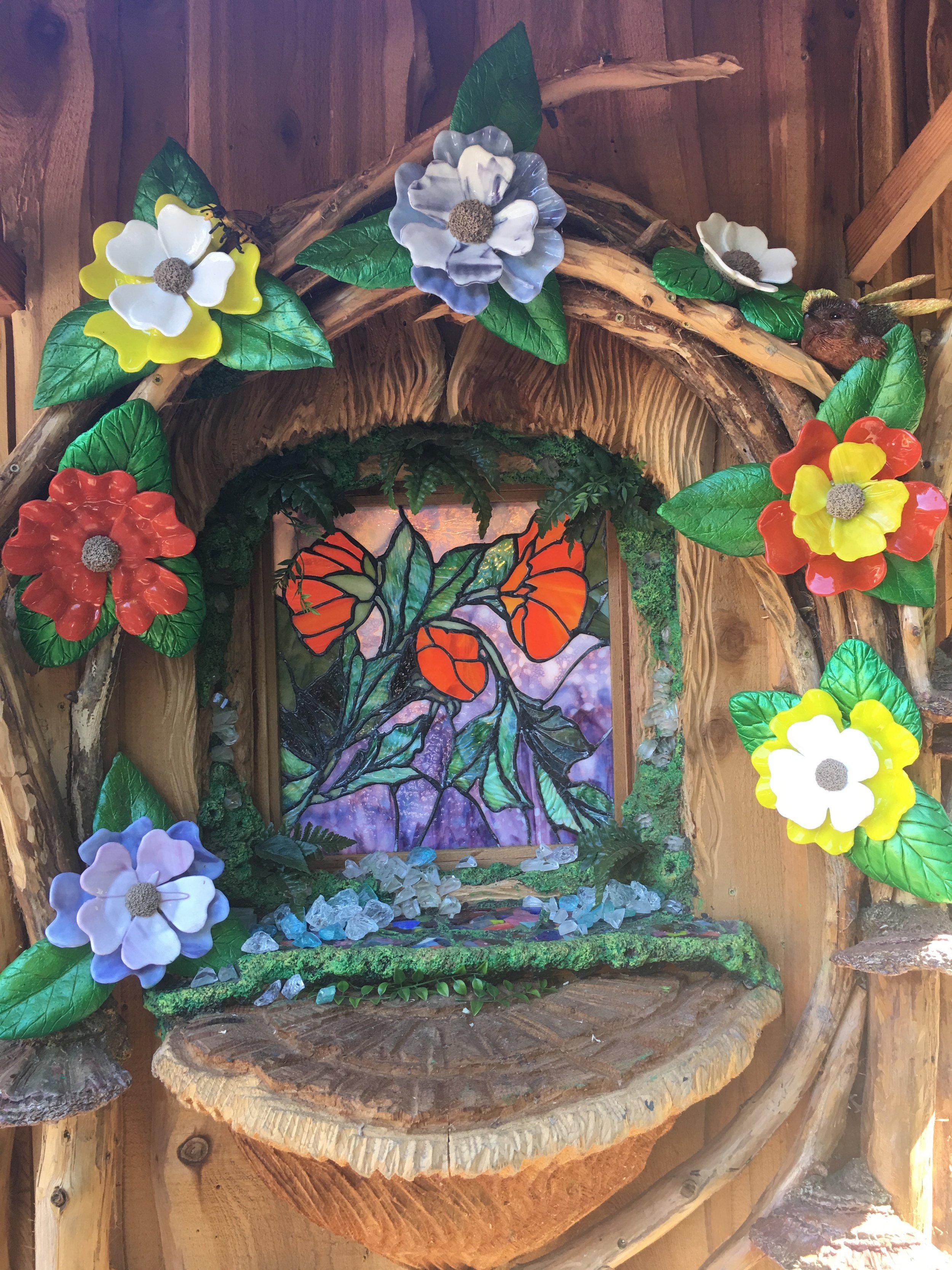 Stained glass window and stained glass sculptural flowers on fairy house.