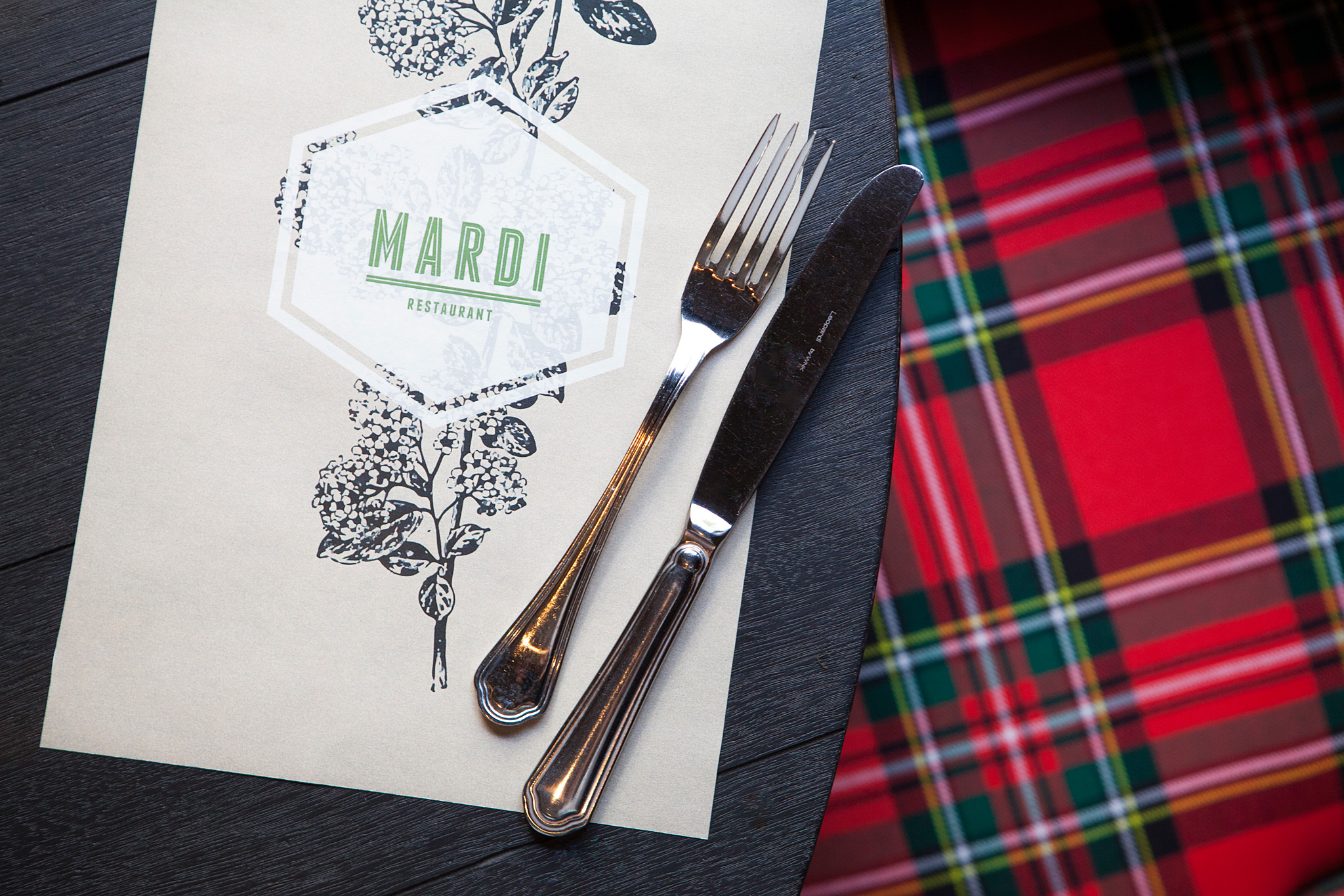 Birds-eye shot of Mardi menu with logo and flower illustration. Fork and knife on corner of menu and corner of table. Red plaid seat also shown.