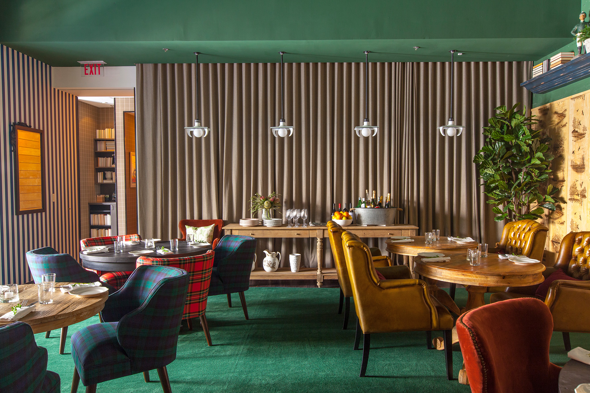 interior shot of private dining room, curtained walls, green carpet, oversized chairs in red plaid, green plaid, yellowed leather, wood tables