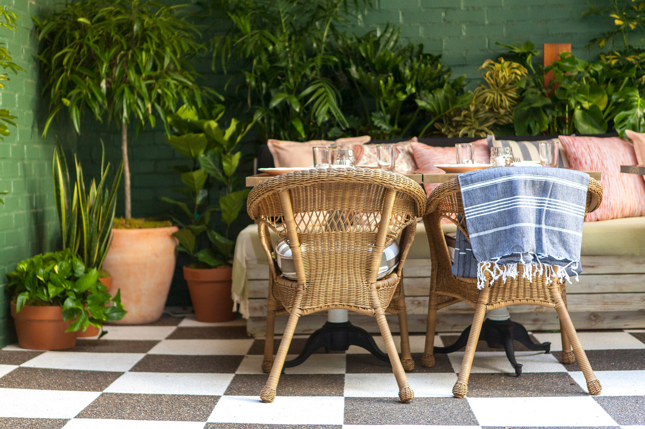corner of courtyard at Mardi  - checkered floor, earth-tone blankets and patterned pillows on bench seating at wood tables with wicker chairs opposite bench. Many green plants surrounding.