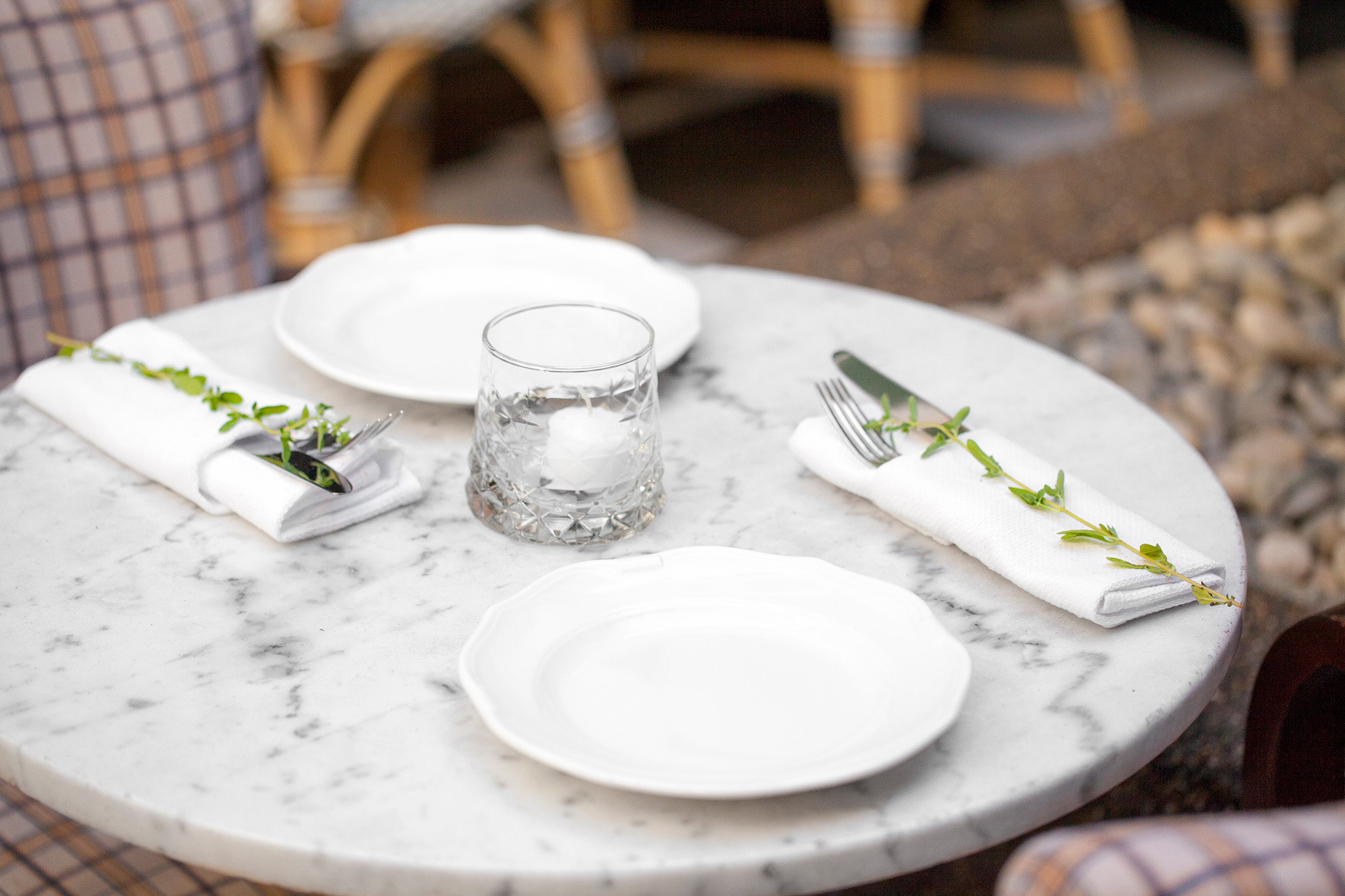 place setting of white dishes on white marble table. Beige plaid chairs.