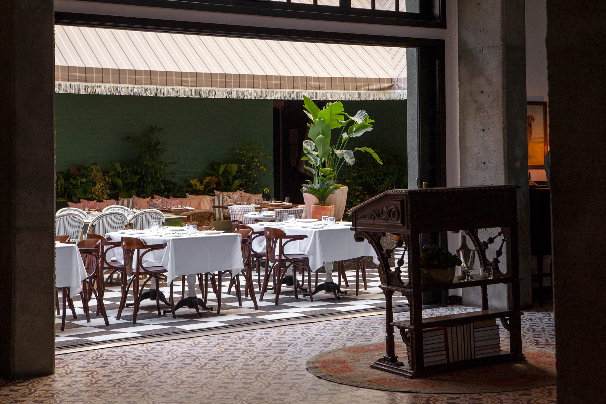 Shot of Mardi courtyard from hotel lobby. Patterned tiles inside lobby, wood host stand on circular carpet, courtyard with checker floor, white tables, wood chairs, a lot of green plants.